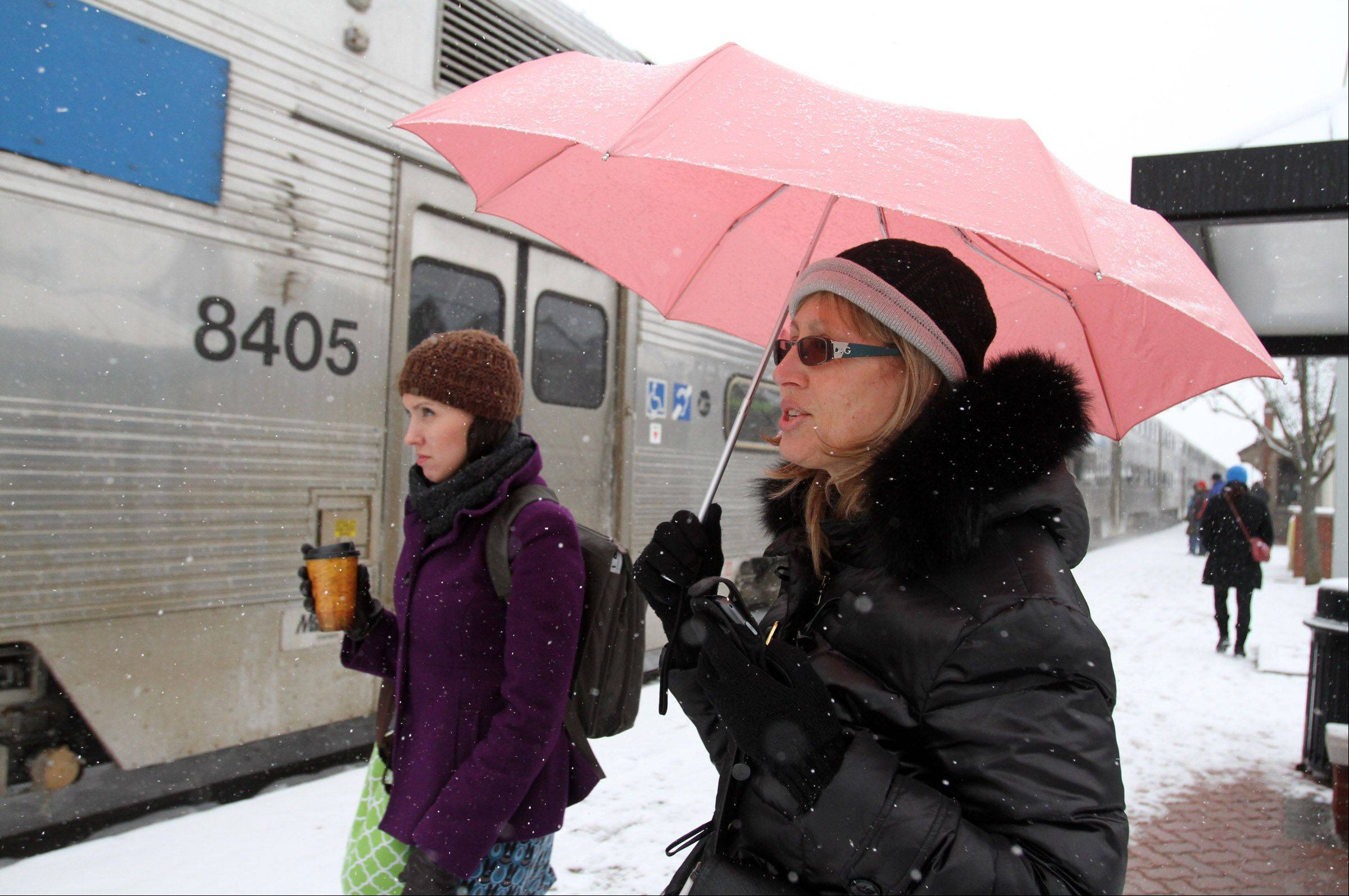 Nadia Rozenberg, of Mount Prospect, uses an umbrella to protect herself from the light snow while waiting to board a train in Mount Prospect Tuesday morning.