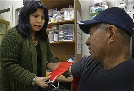 Laura Lopez, left, checks the blood pressure of Santos Aguilar at the Street Level Health Project in Oakland, Calif.