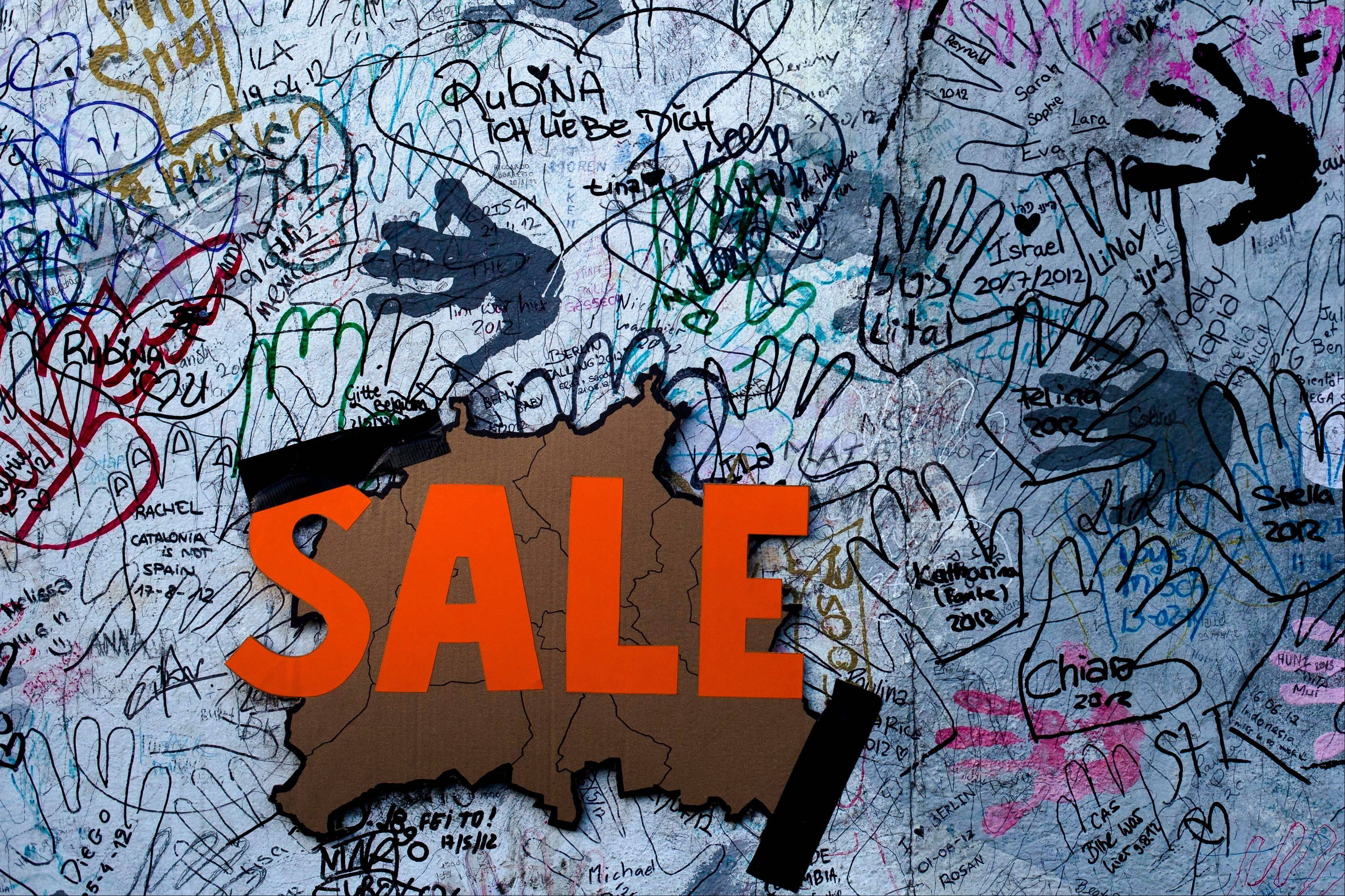 "A ""sale"" sign with the form of Germany's capital Berlin is fixed amid graffiti on the East Side Gallery section of the former Berlin Wall in Berlin on Monday After massive protest, an investor suspended the removal of a section of the historic stretch of the Berlin Wall known as the East Side Gallery to provide access to a riverside plot where luxury condominiums are being built."