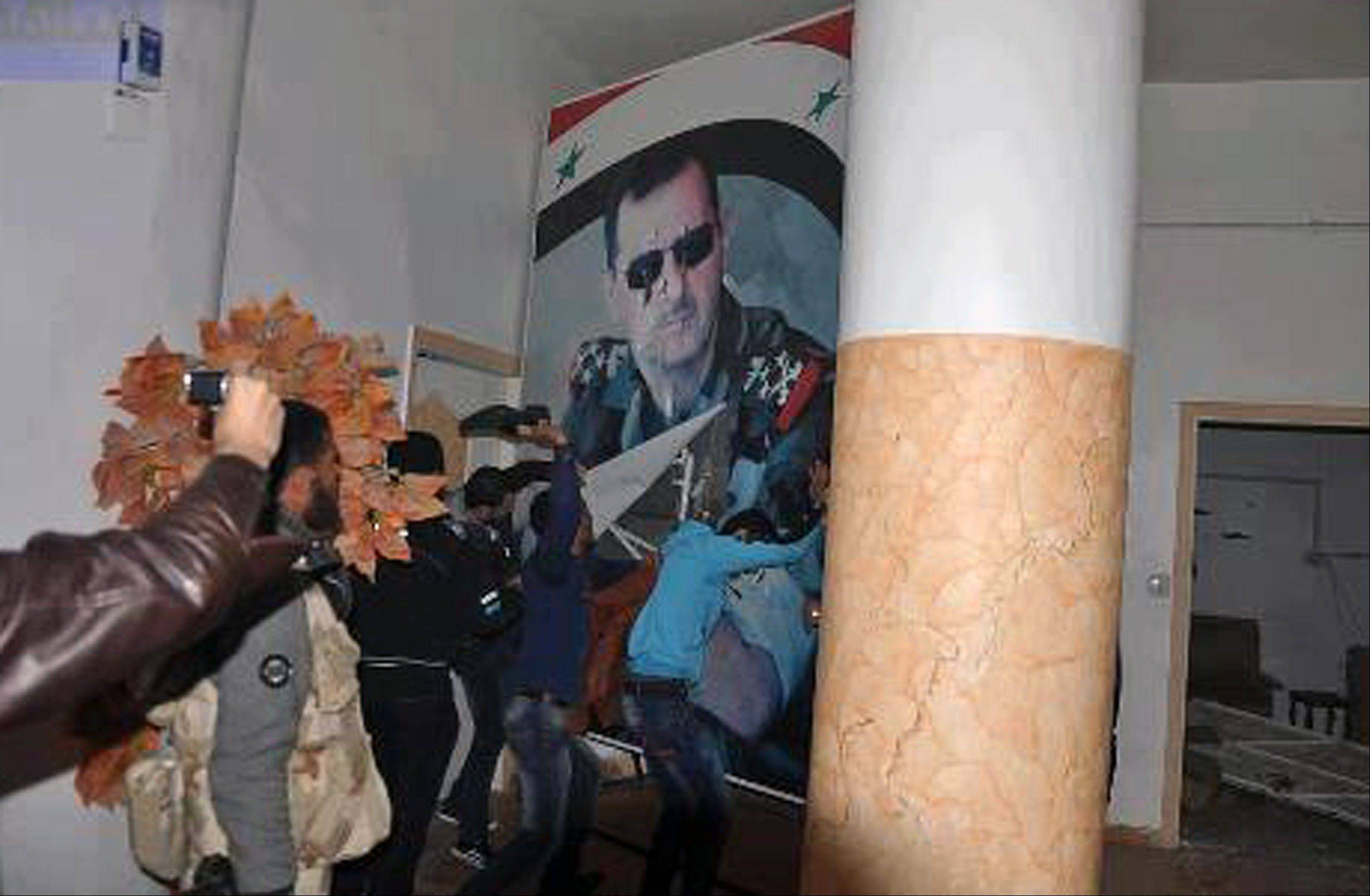 This citizen journalism image provided by Coordination Committee in Kafr Susa, which has been authenticated based on its contents and other AP reporting, shows people tearing down a huge poster of President Bashar Assad and hitting it with their shoes in Raqqa, Syria, Monday.