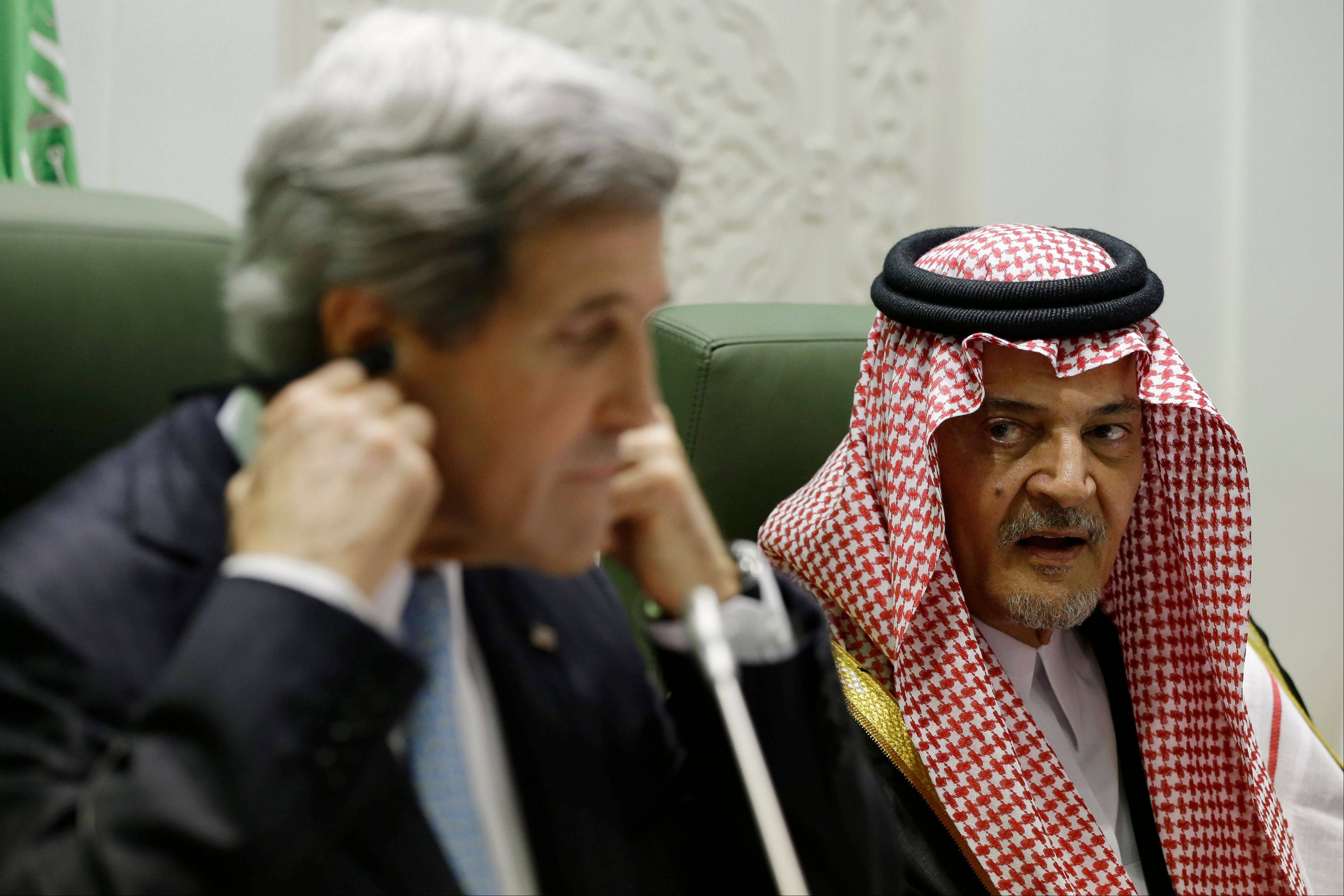 U.S. secretary of state John Kerry adjusts his translation headset as Saudi Foreign Minister Prince Saud al-Faisal speaks Monday during a news conference in Riyadh, Saudi Arabia. From Saudi Arabia, Kerry heads into the homestretch of his lengthy first official trip abroad, traveling next to the United Arab Emirates and then Qatar before returning to Washington on Wednesday.