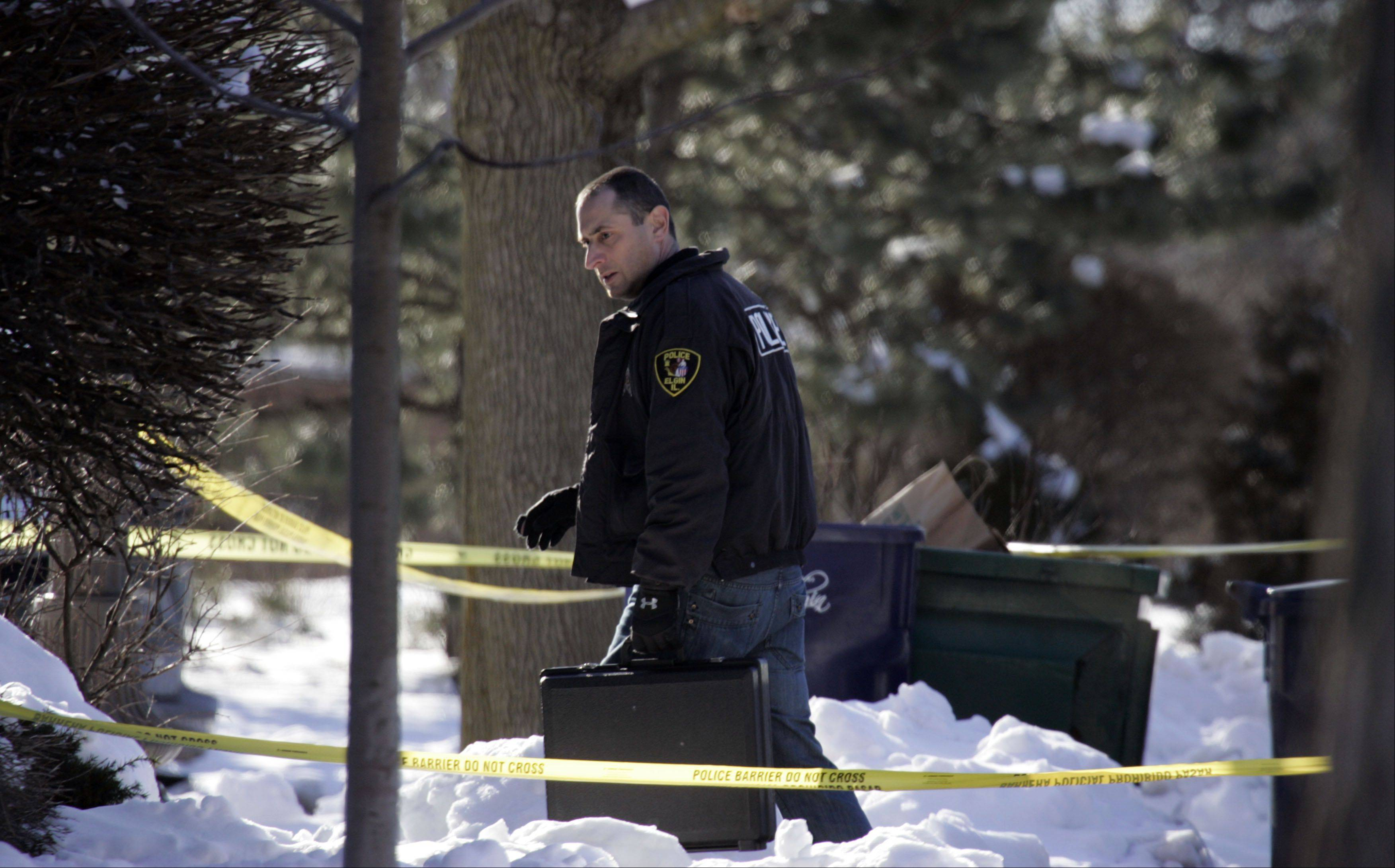 An unidentified Elgin police officer enters a townhouse on Saturday while investigating the murder of 33-year-old Lisa Koziol-Ellis.