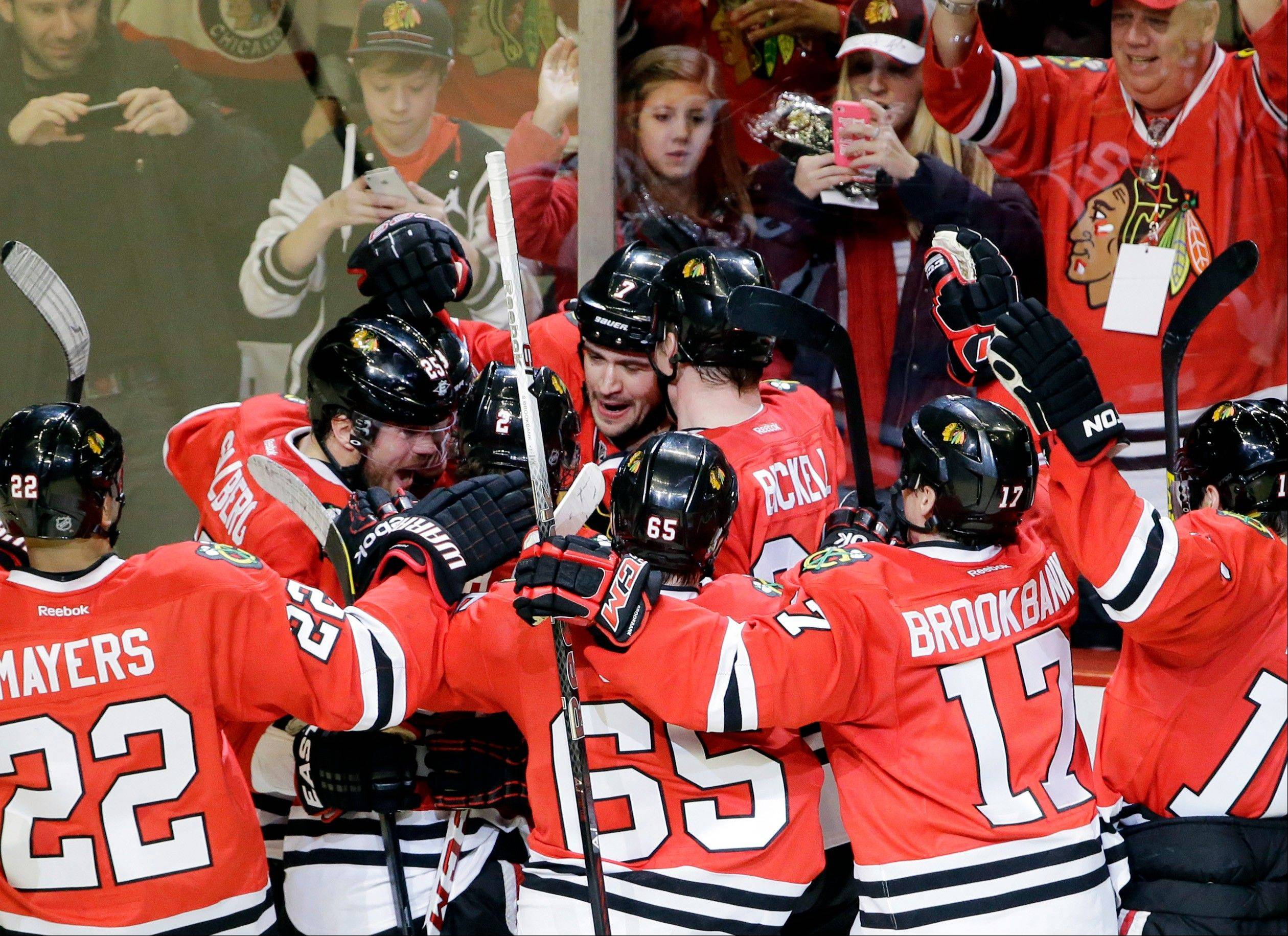 Chicago Blackhawks' Brent Seabrook, center, celebrates with teammates after scoring his game-winning goal during the overtime of an NHL hockey game against the Columbus Blue Jackets in Chicago, Friday, March 1, 2013. The Blackhawks won 4-3.