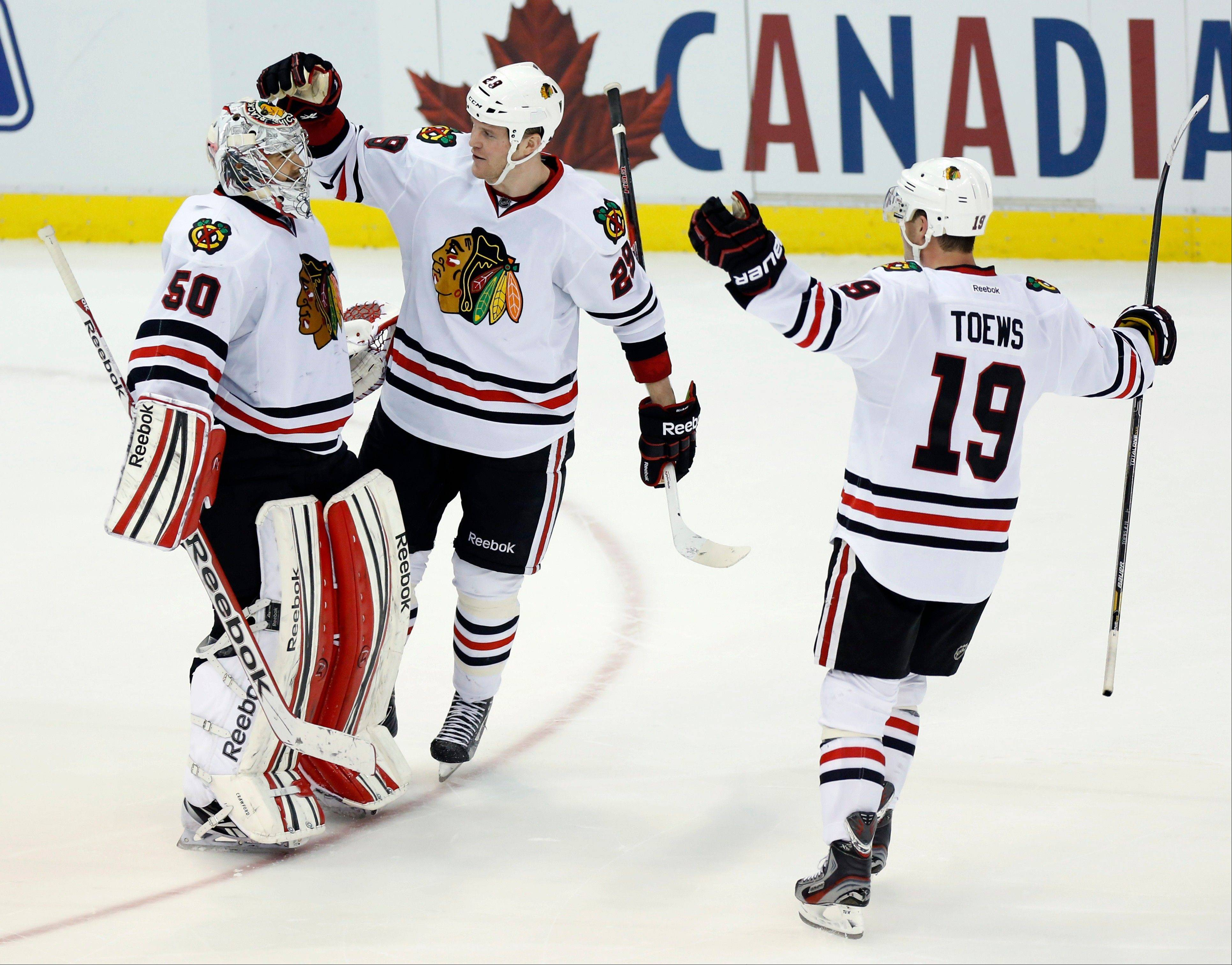 Blackhawks goalie Corey Crawford (50) is congratulated by left wing Bryan Bickell (29) and center Jonathan Toews (19) after defeating the Detroit Red Wings 2-1 in a shootout on Sunday. The Hawks will try to extend their point streak to 29 games when they take on Minnesota.