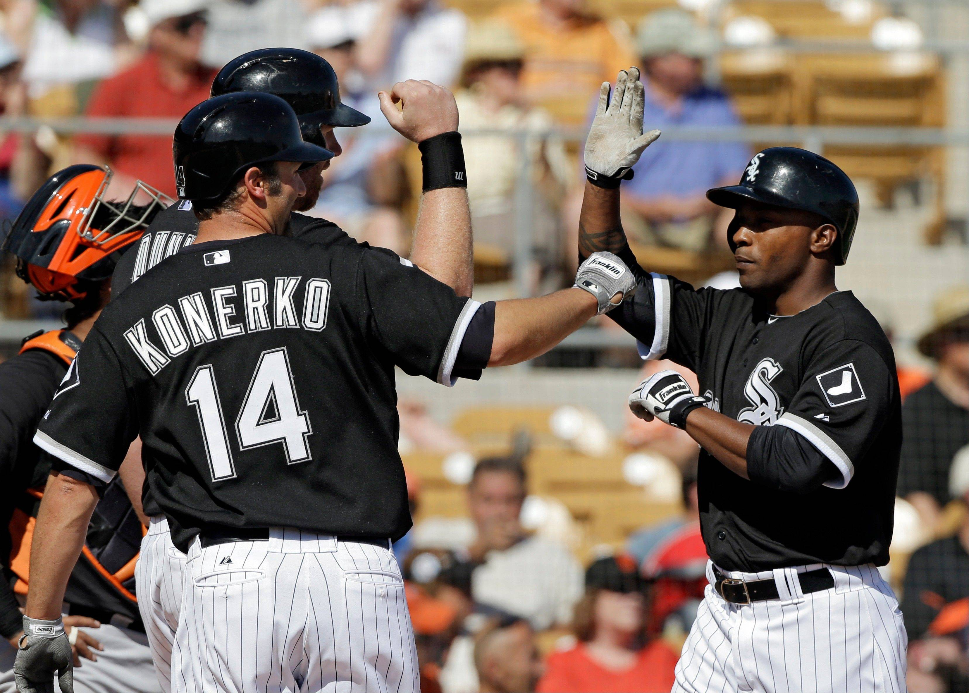 Chicago White Sox's Dewayne Wise, right, is welcomed home by Paul Konerko (14) and Adam Dunn after they score on Wise's three-run home run in the fourth inning of an exhibition spring training baseball game against the San Francisco Giants Monday, March 4, 2013, in Glendale, Ariz.
