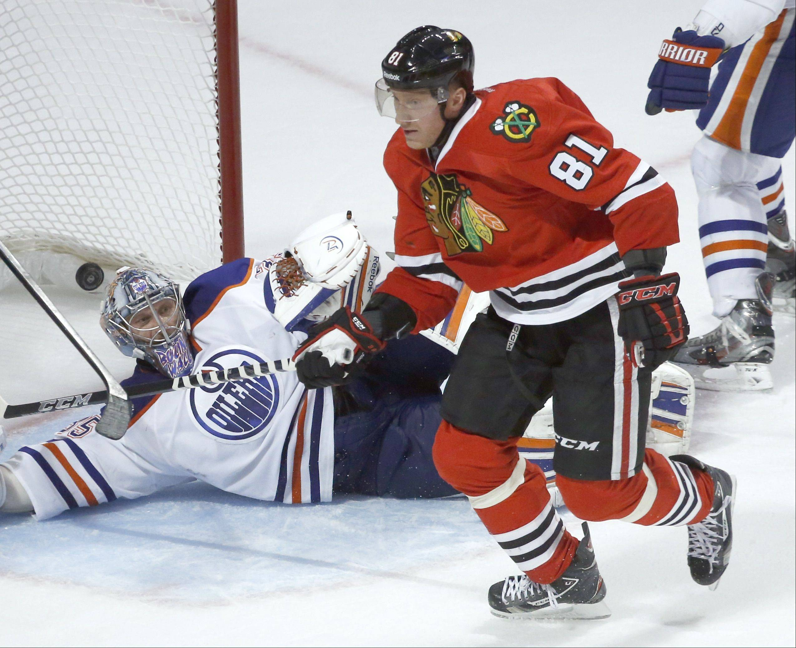 Marian Hossa (81) begins to celebrate after scoring the winning goal past Edmonton Oilers goalie Nikolai Khabibulin in overtime Feb. 25 at the United Center. The Blackhawks won 3-2.