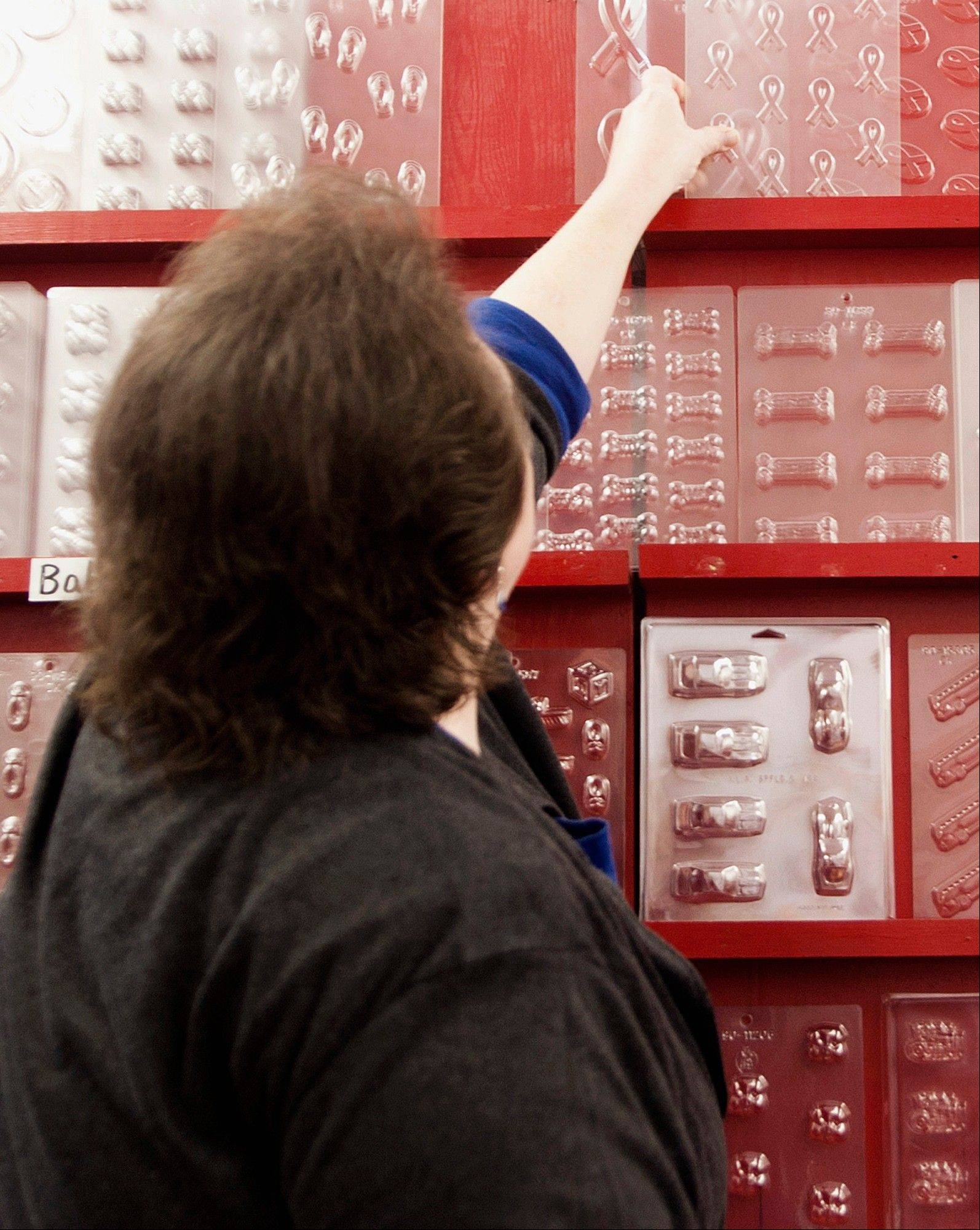 Lisa McCormack sorts through various candy molds at the Decorator Grocery in Peoria.
