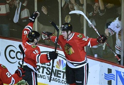 Blackhawks center Marcus Kruger and left wing Bryan Bickell celebrate after Bickell scored during the first period of an NHL hockey game against the Minnesota Wild, Tuesday at the United Center.