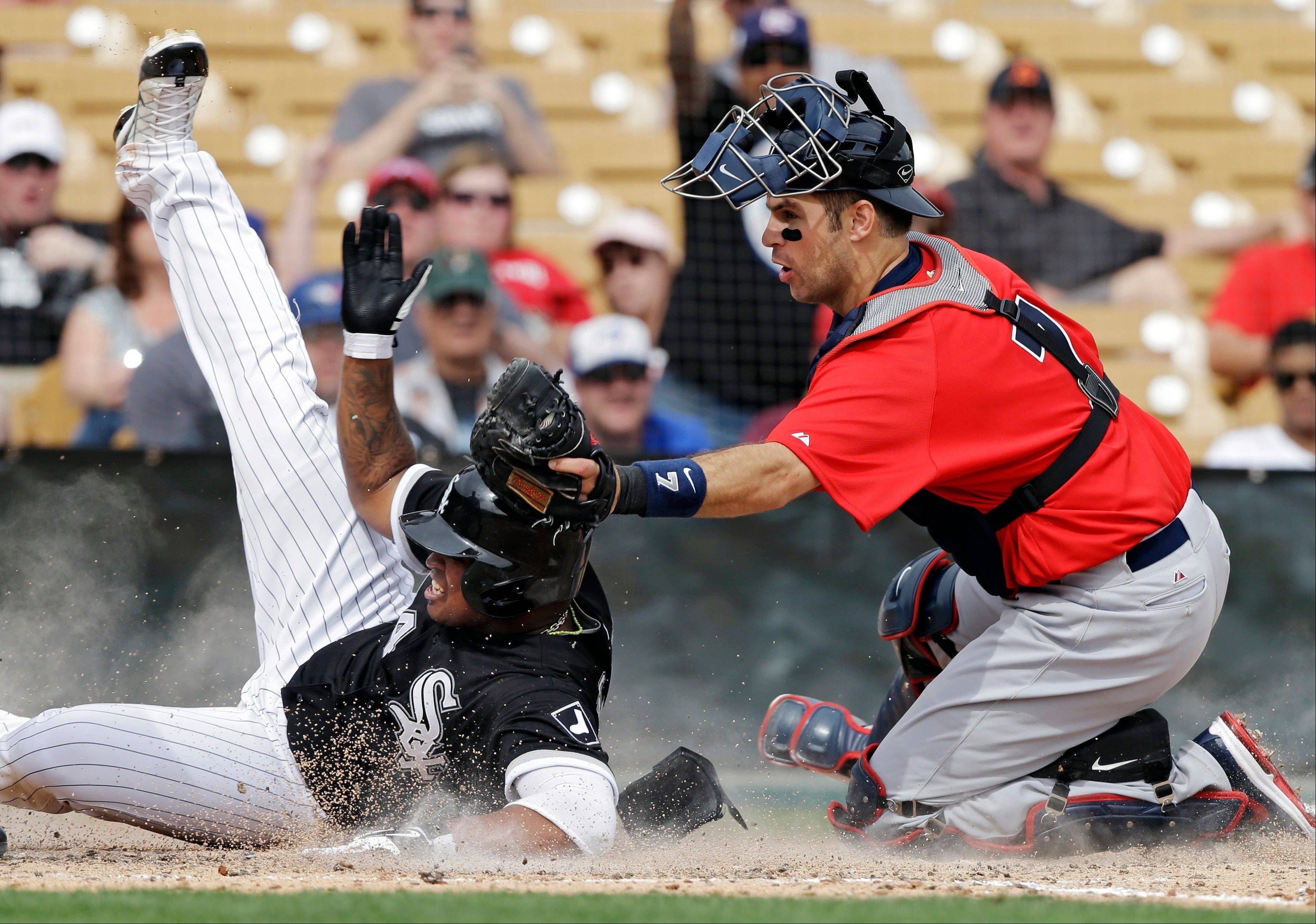 United States catcher Joe Mauer, right, tags out Chicago White Sox's Dayan Viciedo trying to score from second on a single by Gordon Beckham in the fourth inning of an exhibition baseball game Tuesday, March 5, 2013, in Glendale, Ariz. The game is the first of two exhibitions the United States will play leading up the the start of the World Baseball Classic. (AP Photo/Mark Duncan)