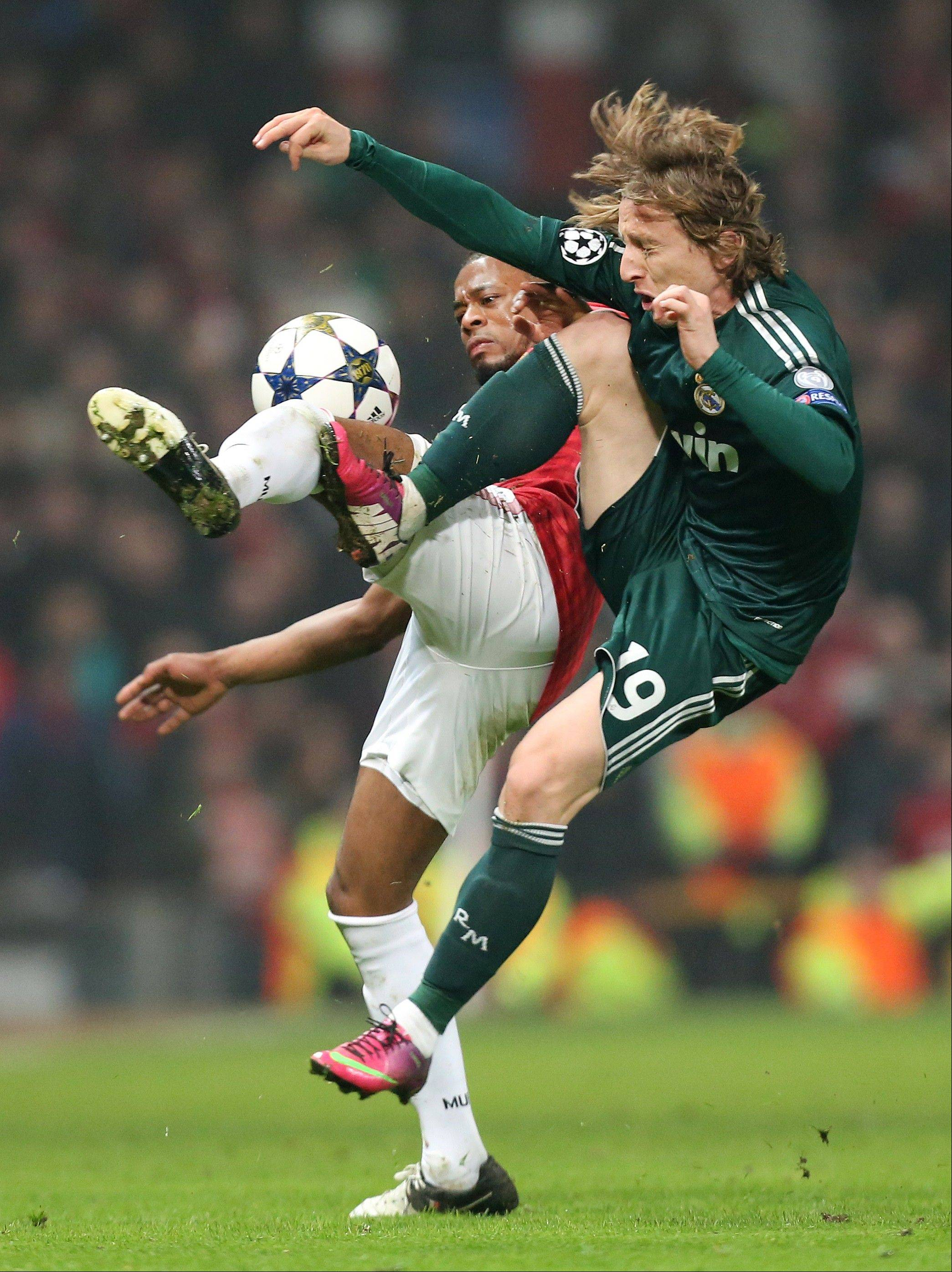 Manchester United's Patrice Evra, rear, challenges Real Madrid's Luka Modric from Croatia during their Champions League round of 16 soccer match at Old Trafford Stadium, Manchester, England, Tuesday, March 5, 2013. (AP Photo/Jon Super)