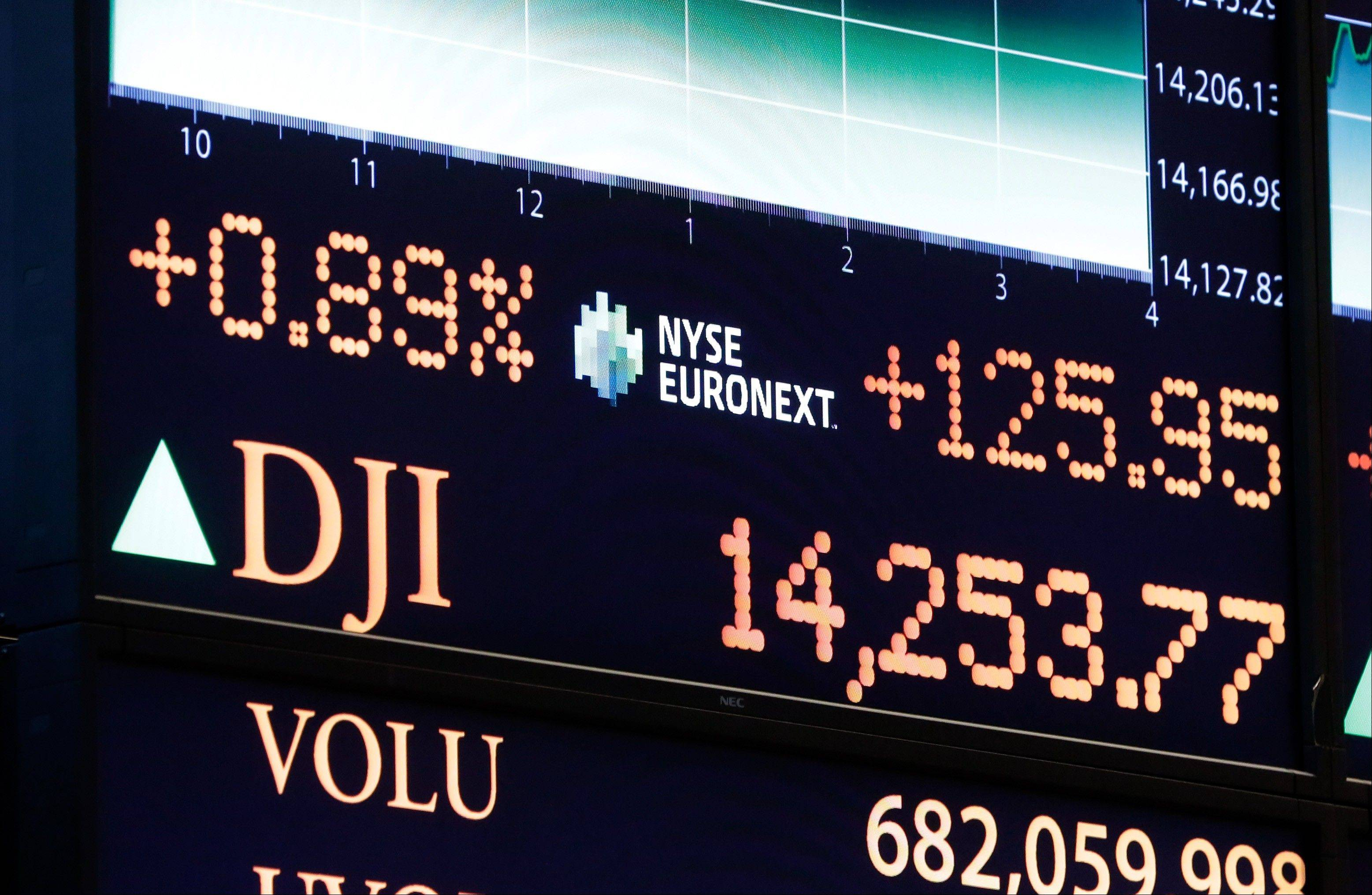 A board on the floor of the New York Stock Exchange shows the closing number for the Dow Jones industrial average Tuesday, closing at an all-time high by beating the previous record it set in October 2007.