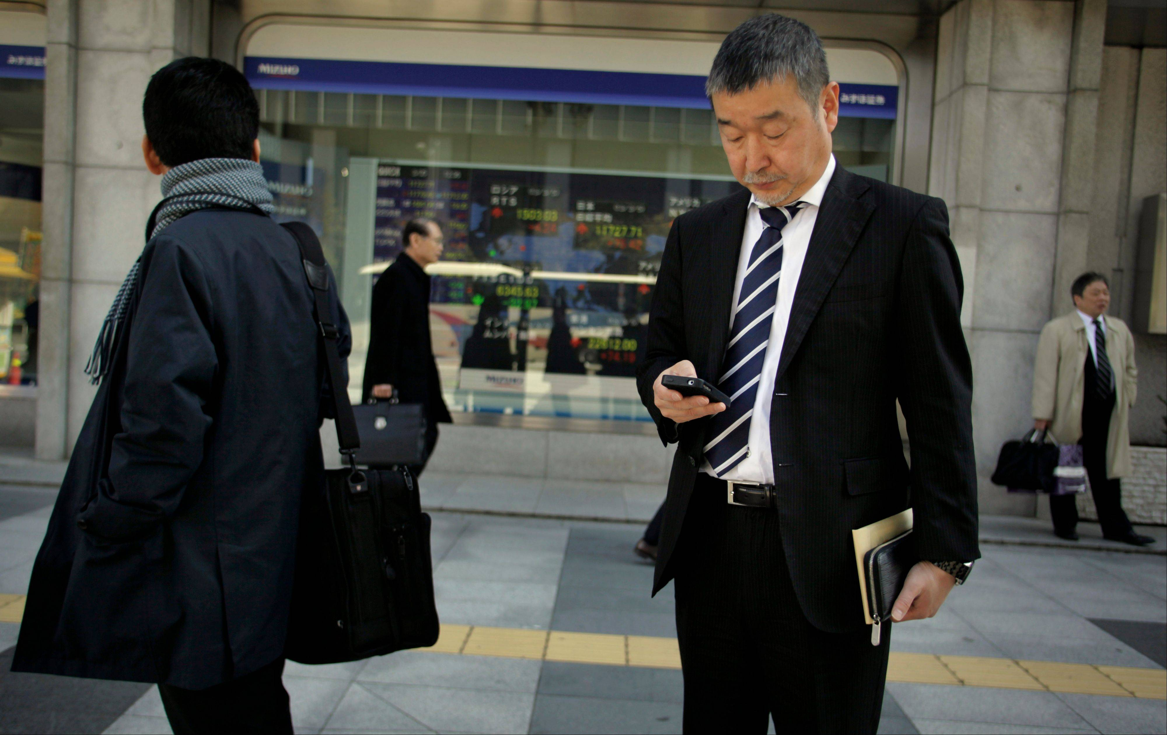 A man checks his cell phone outside a securities firm in Tokyo, Tuesday.