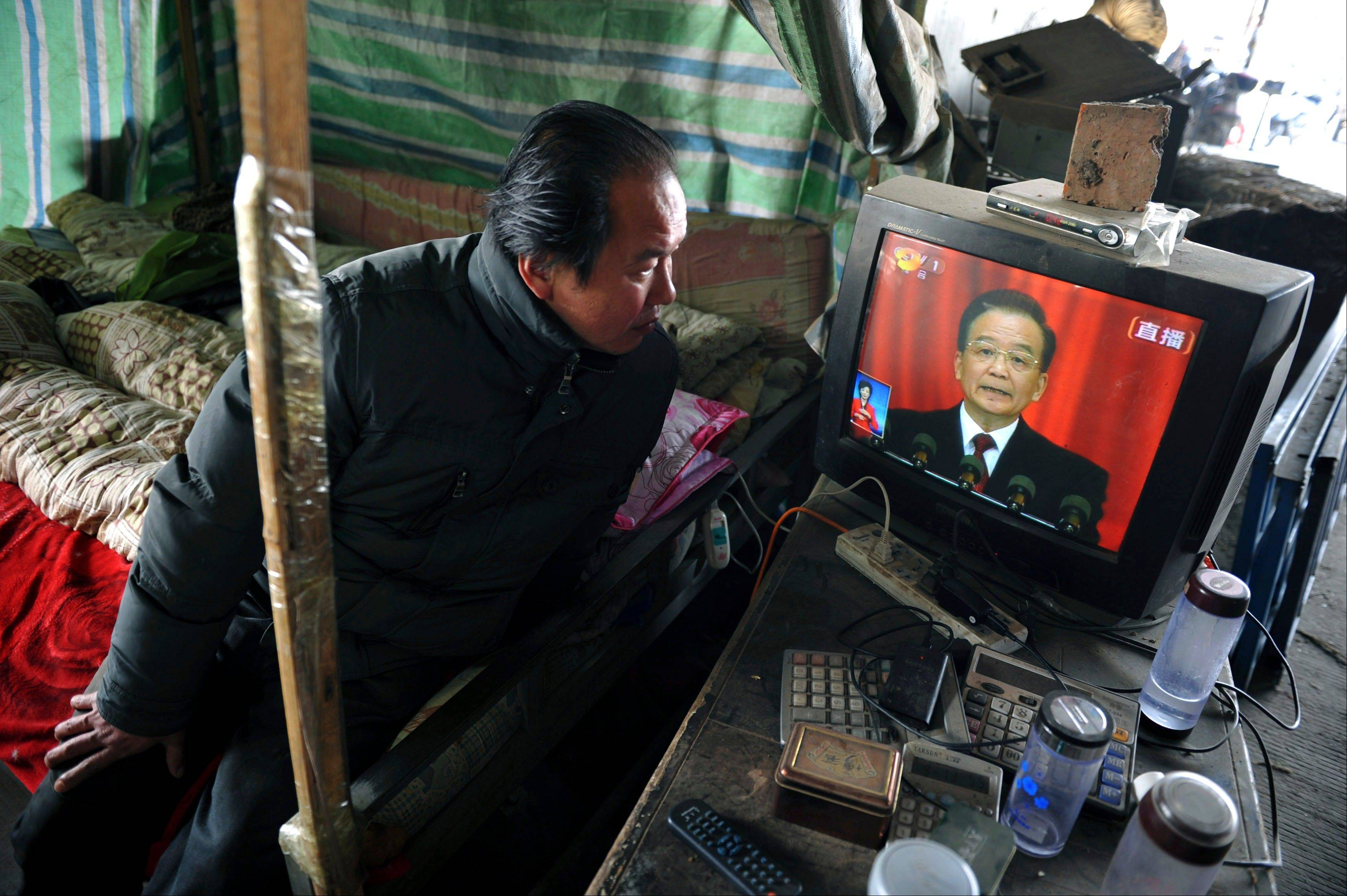 A vendor watches the live telecast of the annual government work report by outgoing Premier Wen Jiabao on a television in a vegetable wholesale market in Fuyang in central China's Anhui province Tuesda.
