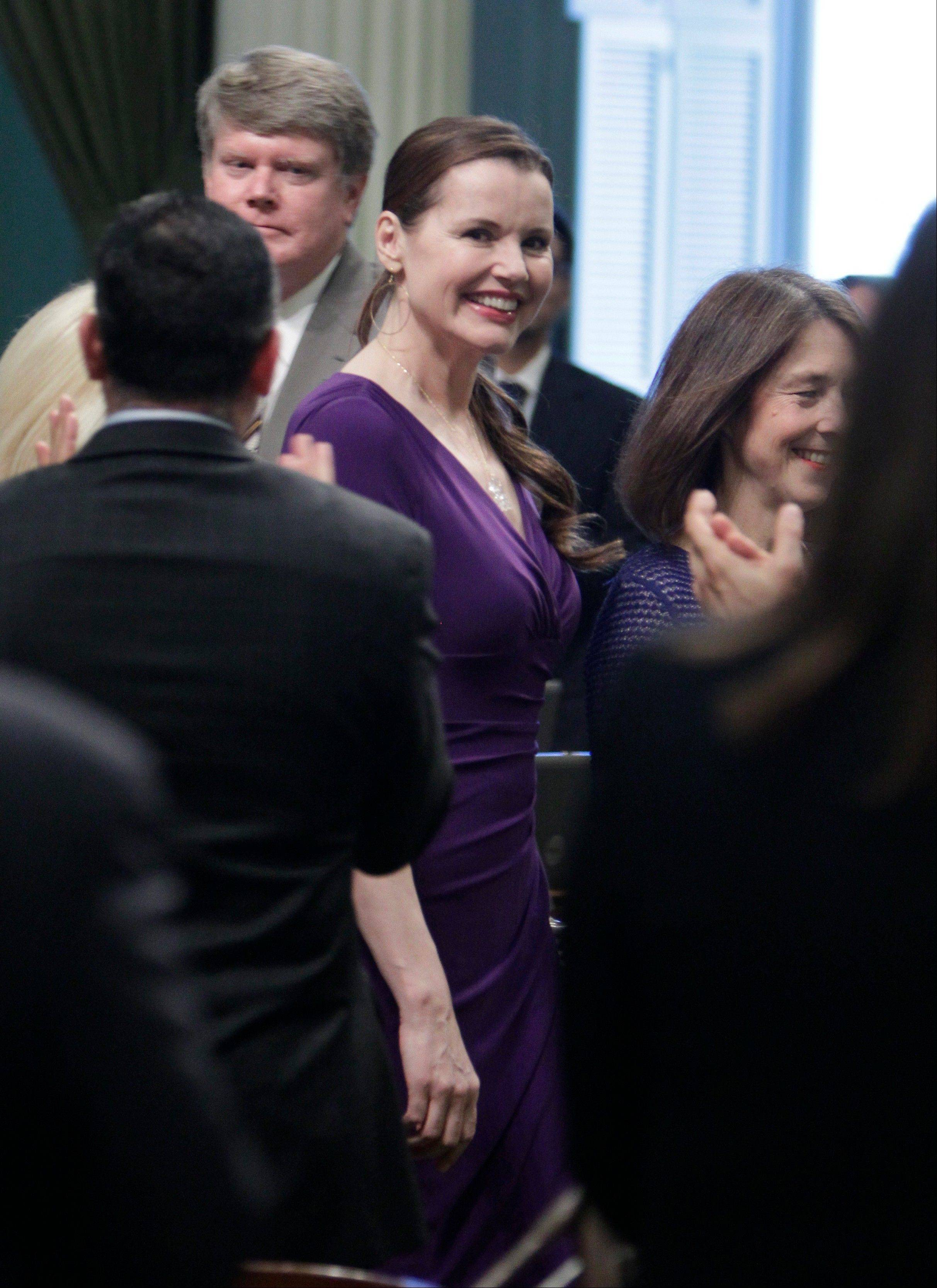Actress Geena Davis receives a standing ovation from members of the state Assembly as she is escorted down the center aisle by Assemblywoman Nancy Skinner, D-Berkeley, right, at the Capitol in Sacramento, Calif., Monday. Davis, who is the chairwoman of the Commission on the Status of Women, was one of several women honored for their accomplishments.