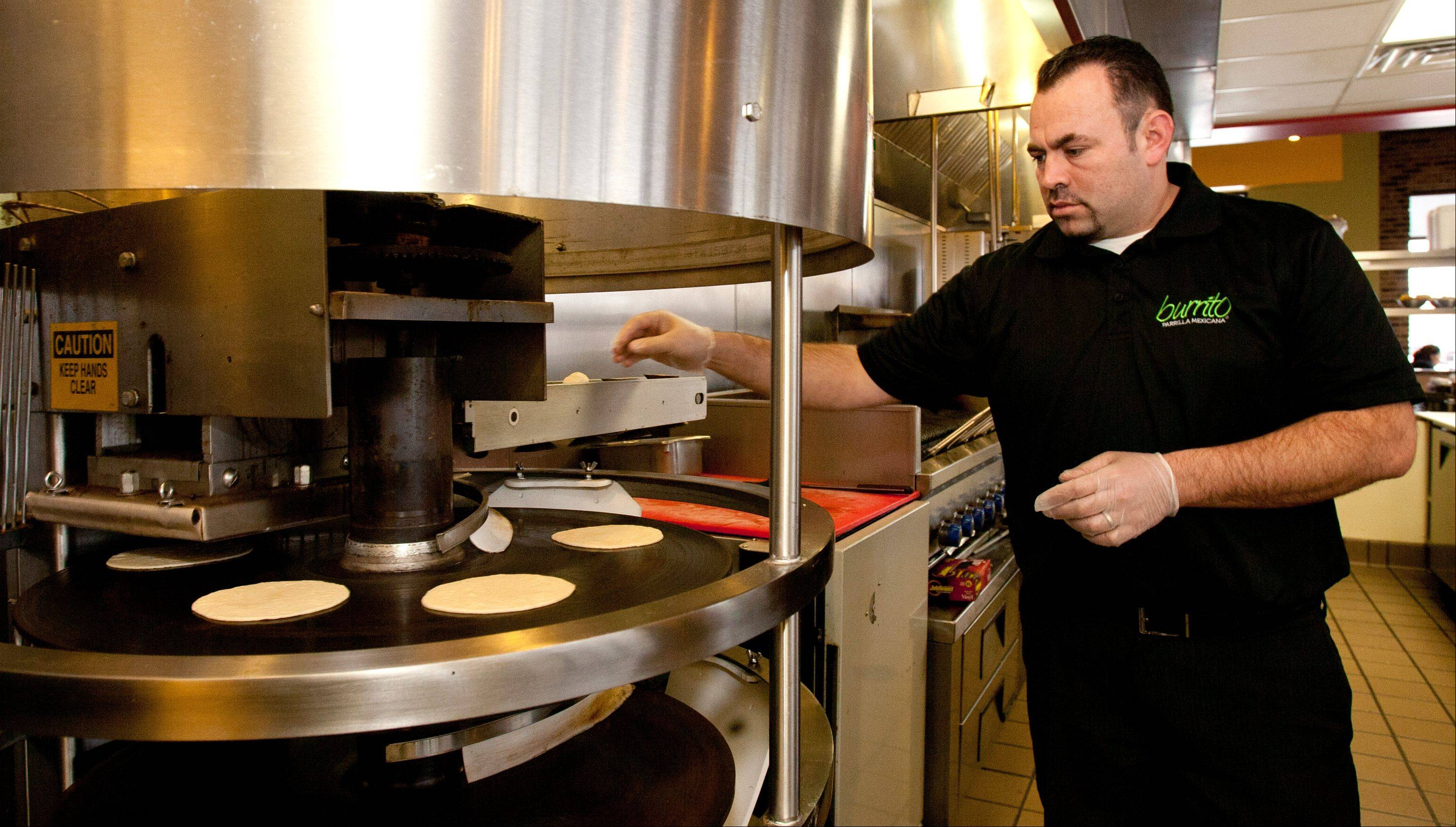 Burrito Parrilla Mexicana owner David Perez monitors a tortilla maker.