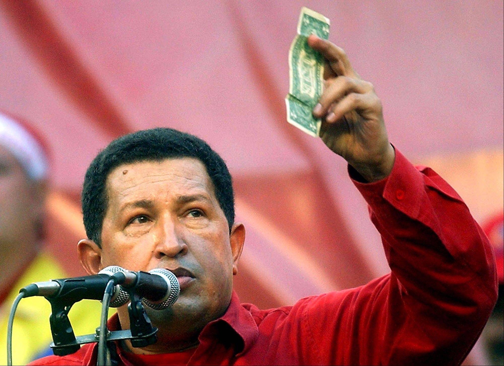 On Jan. 23, 2005, Venezuela's President Hugo Chavez helds up a U.S. dollar bill and challenged U.S. President George W. Bush to bet which of them would remain in power longer at a rally in Caracas. Chavez died on Tuesday at age 58 after a nearly two-year bout with cancer.