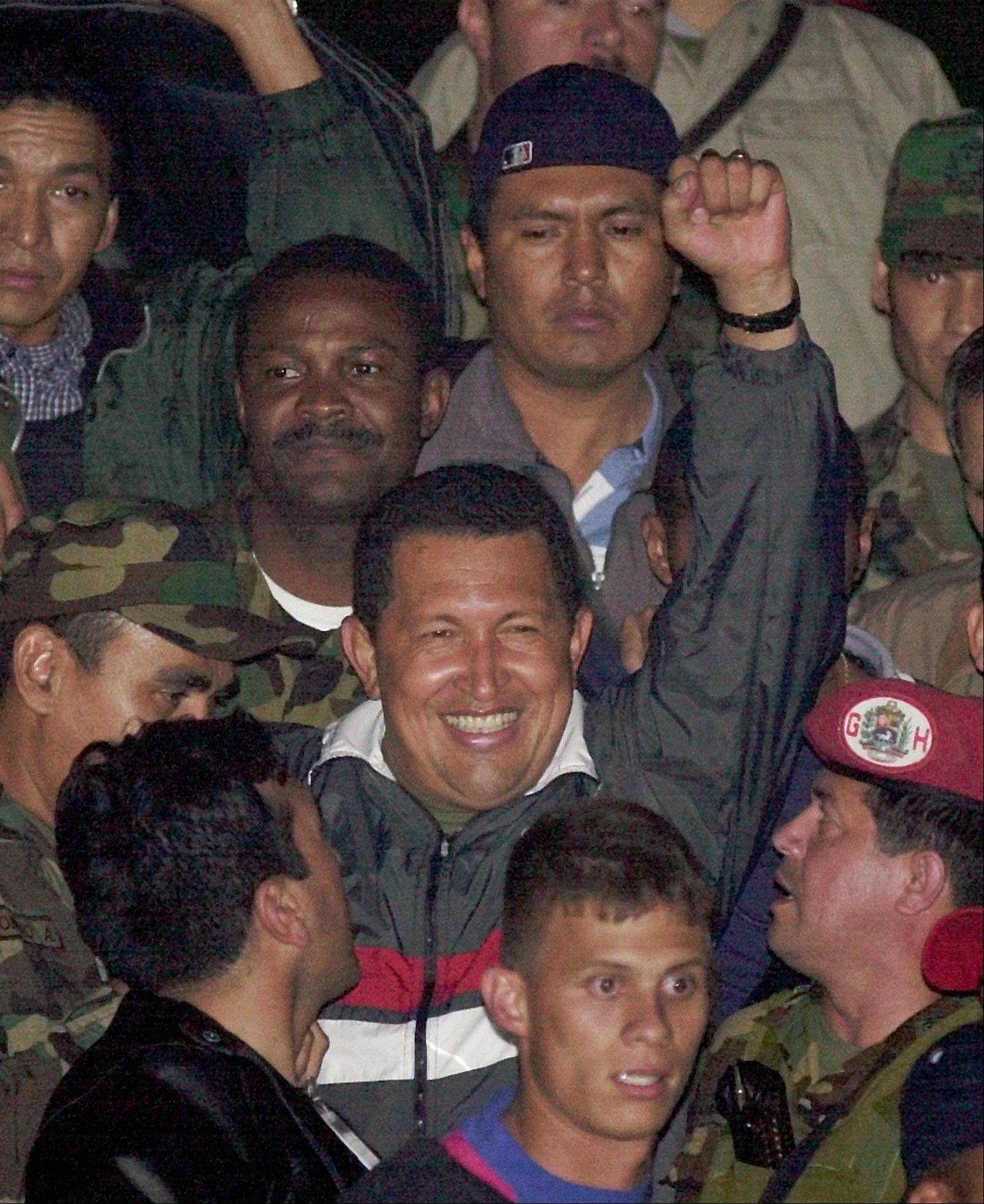 In this April 14, 2002 file photo, Venezuela's President Hugo Chavez gestures to supporters as he arrives to Miraflores presidential palace after being freed by his military captors two days after the military announced he had resigned in Caracas, Venezuela.