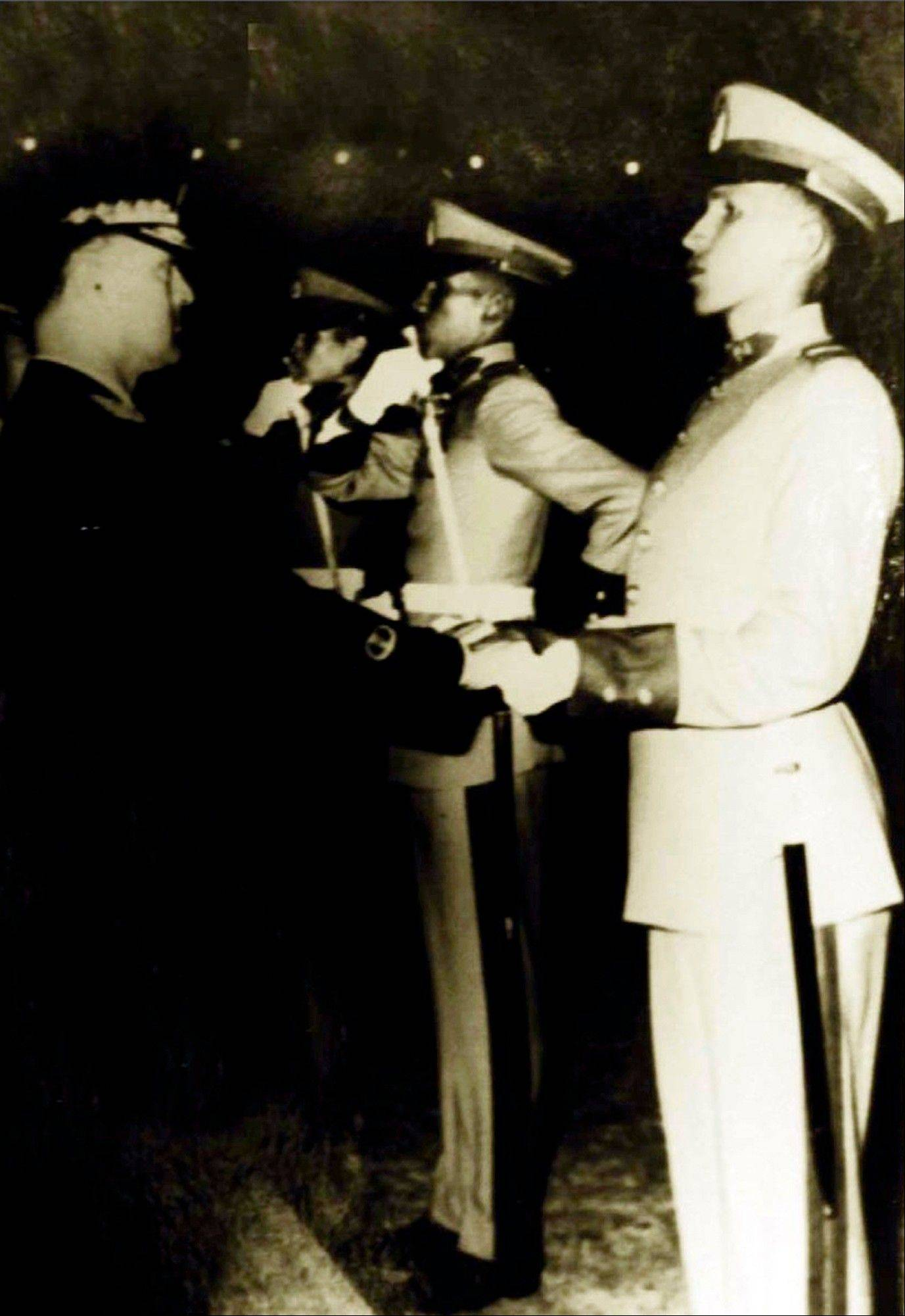 In this April 1971 photo released by Miraflores Press Office, Venezuela's President Hugo Chavez, right, receives a dagger during his ceremony to enter the military academy in Caracas, Venezuela.