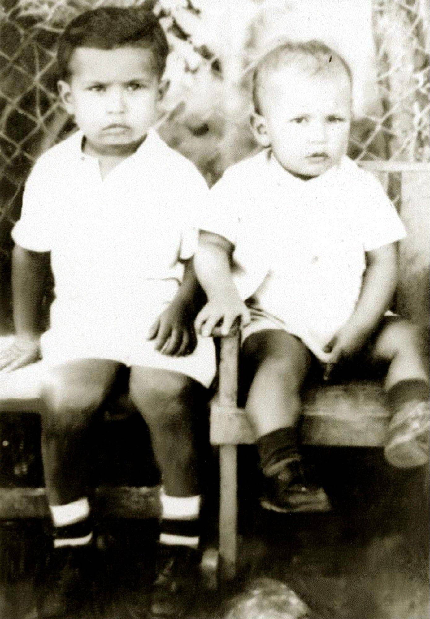 In this undated photo released by Miraflores Press Office, Hugo Chavez, right, sits with his brother Adam in Barinas, Venezuela.