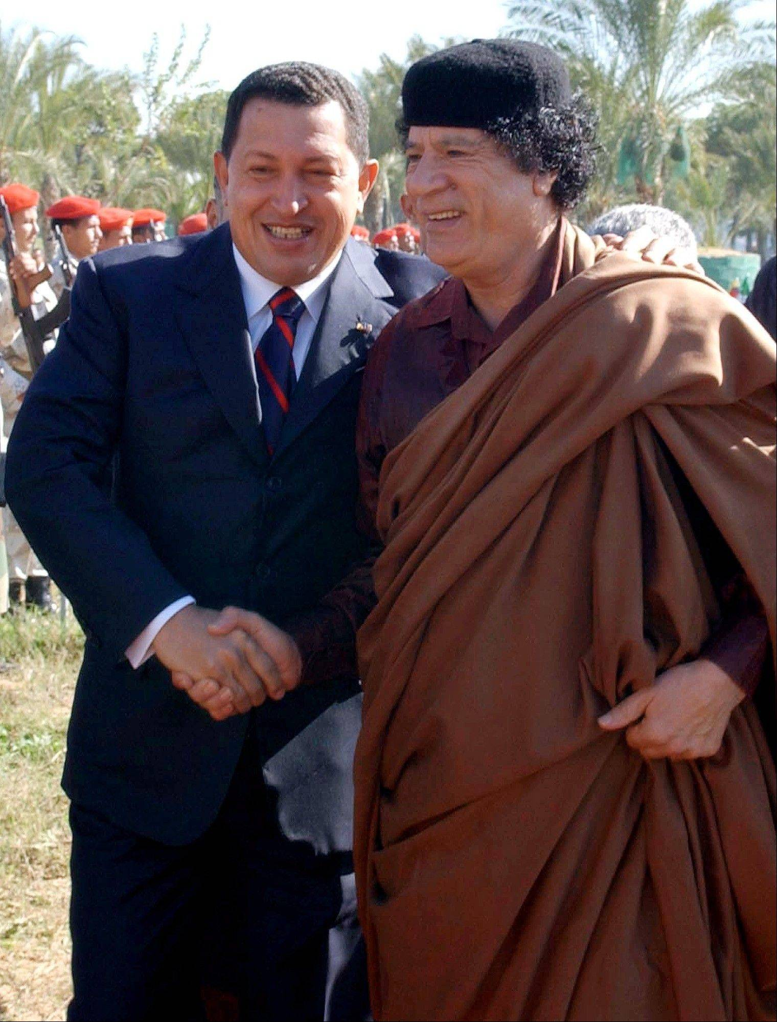 In this Nov. 24, 2004 file photo released by Miraflores Presidential Press Office, Libyan leader Moammar Gadhafi, right, greets Venezuela's President Hugo Chavez in Tripoli, Libya.