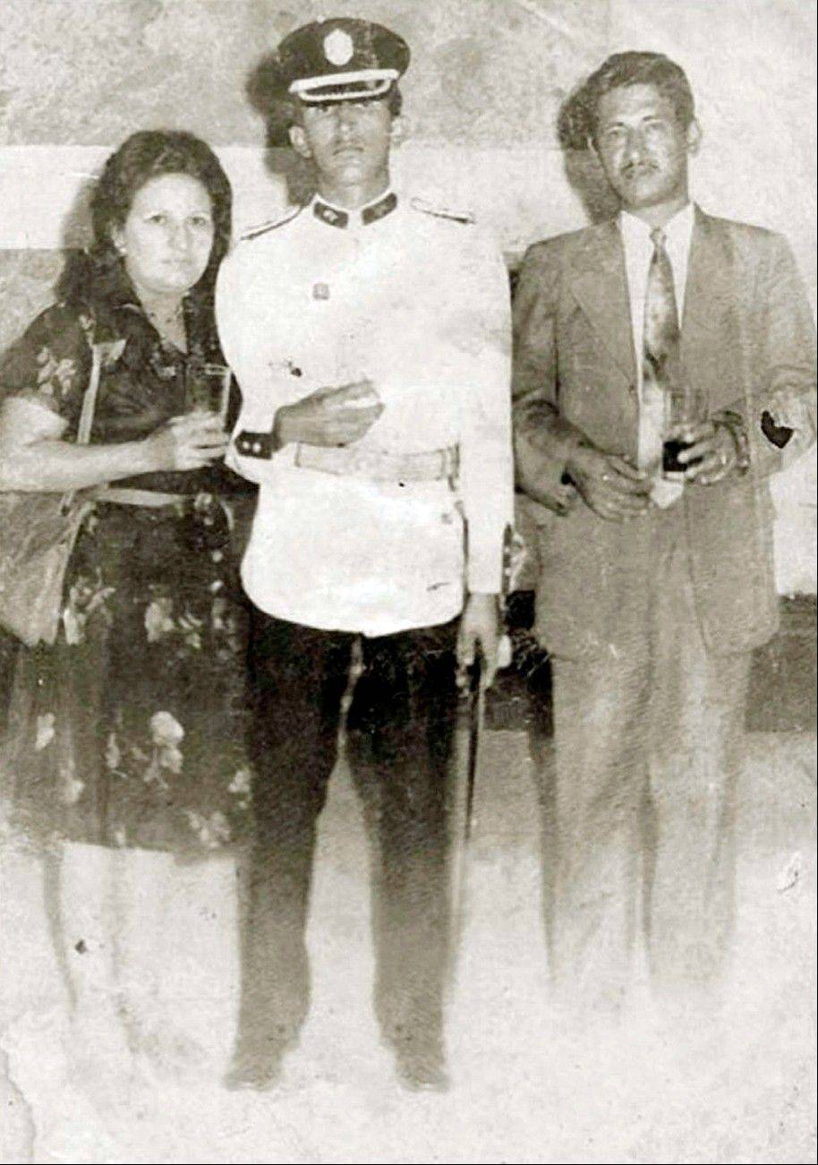 In this July 5, 1975 photo released by Miraflores Press Office, Hugo Chavez, center, poses with his mother Elena Frias and father Hugo de los Reyes Chavez at his graduation from the military academy in Caracas, Venezuela.