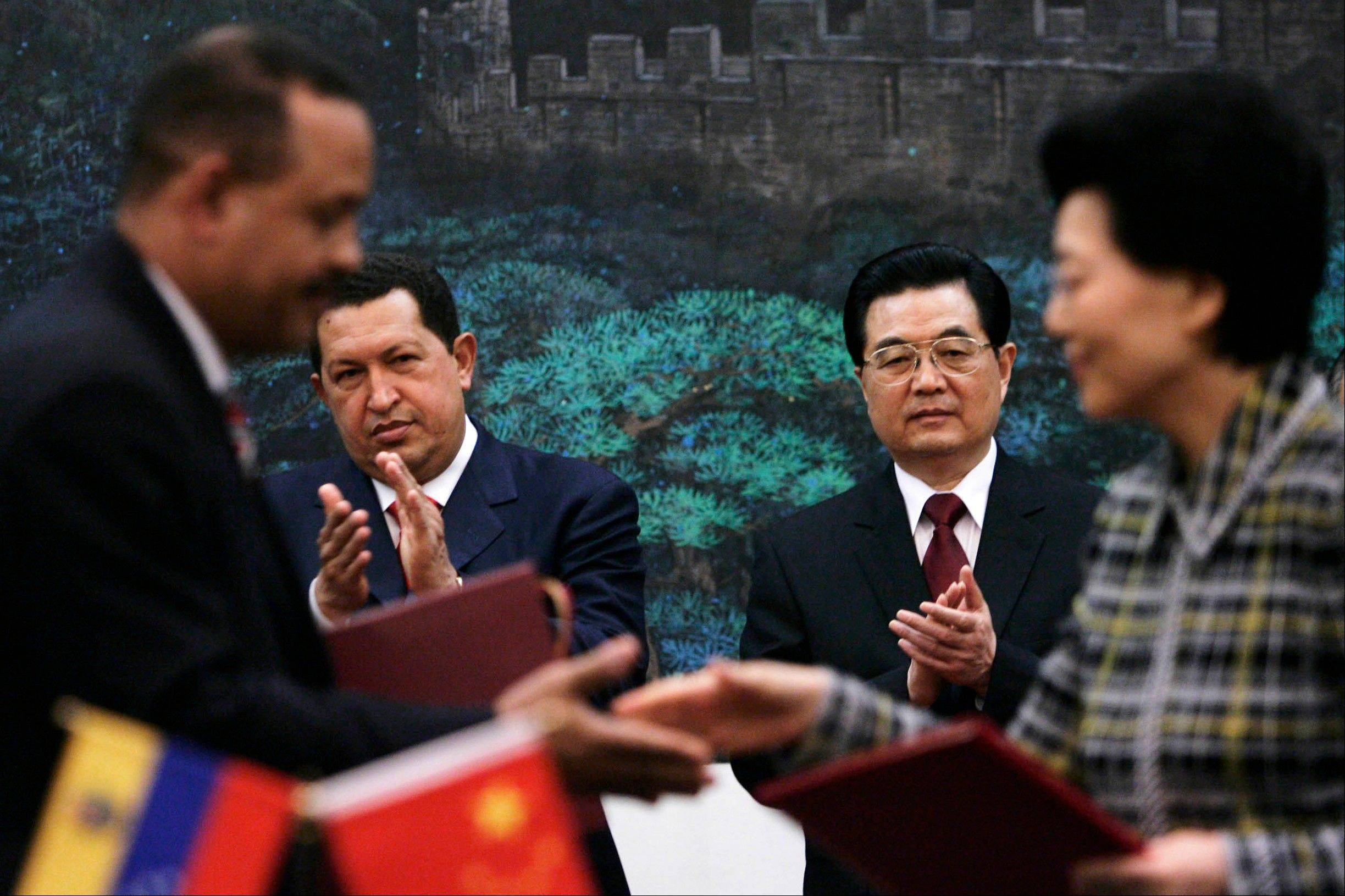 In this Sept. 24, 2008 file photo, Chinese President Hu Jintao, behind right, and Venezuela's President Hugo Chavez, behind left, applaud during an agreement signing ceremony at the Great Hall of the People in Beijing, China.