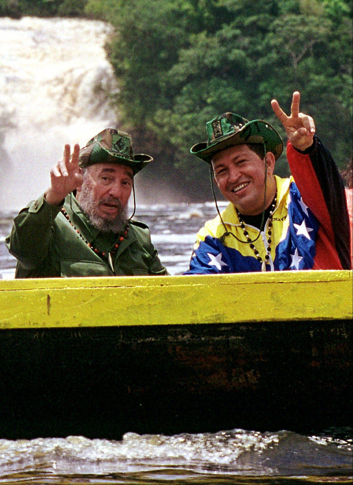 In this Aug. 12, 2001 file photo released by Miraflores Press Office, Cuba's President Fidel Castro, left, and Venezuela's President Hugo Chavez wave to a crowd while touring Canaima National Park in eastern Venezuela in a canoe.