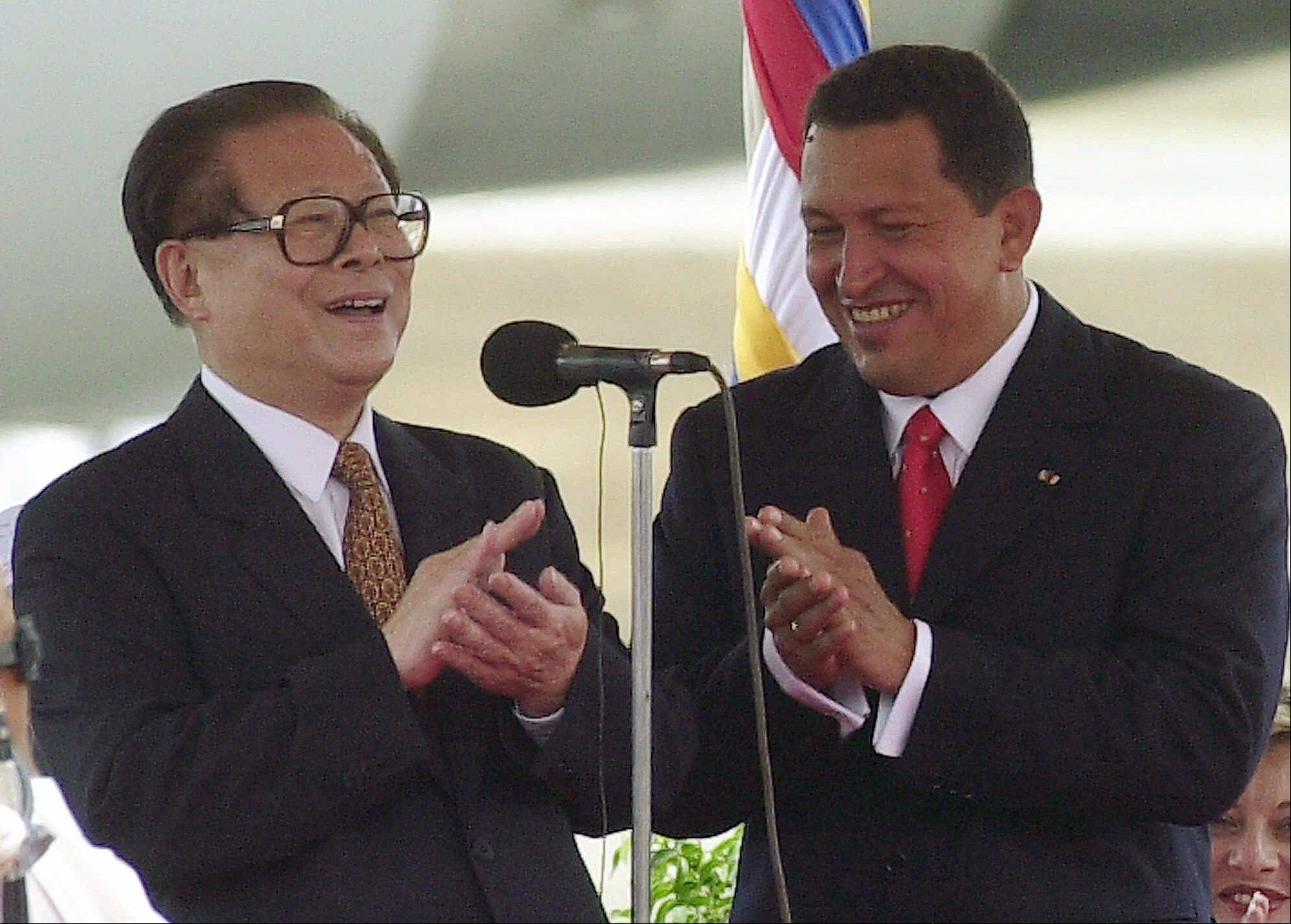 In this April 15, 2001 file photo, China's President Jiang Zemin, left, and Venezuela's President Hugo Chavez applaud during a welcome ceremony at Simon Bolivar International Airport in Maiquetia, Venezuela.