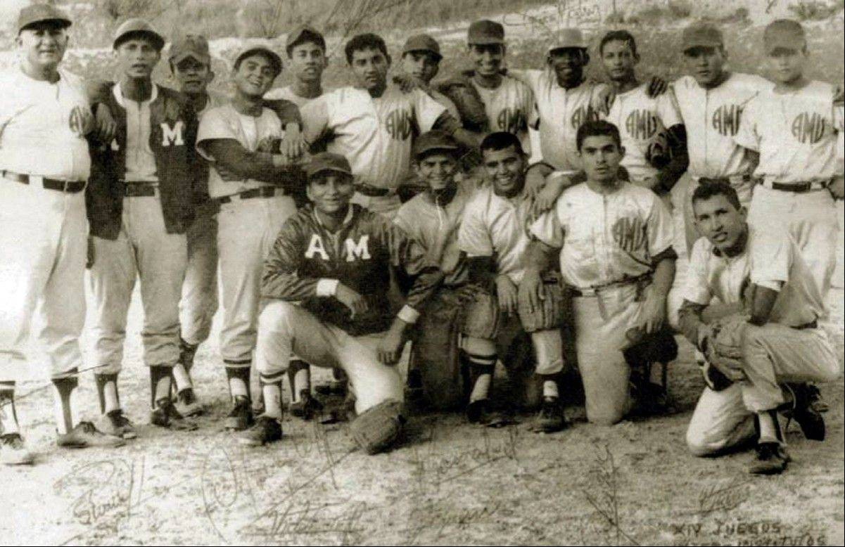 In this March 1972 photo released by Miraflores Press Office, Hugo Chavez, bottom row, right, poses with his baseball teammates during the internal games at the Military Academy in Caracas, Venezuela.