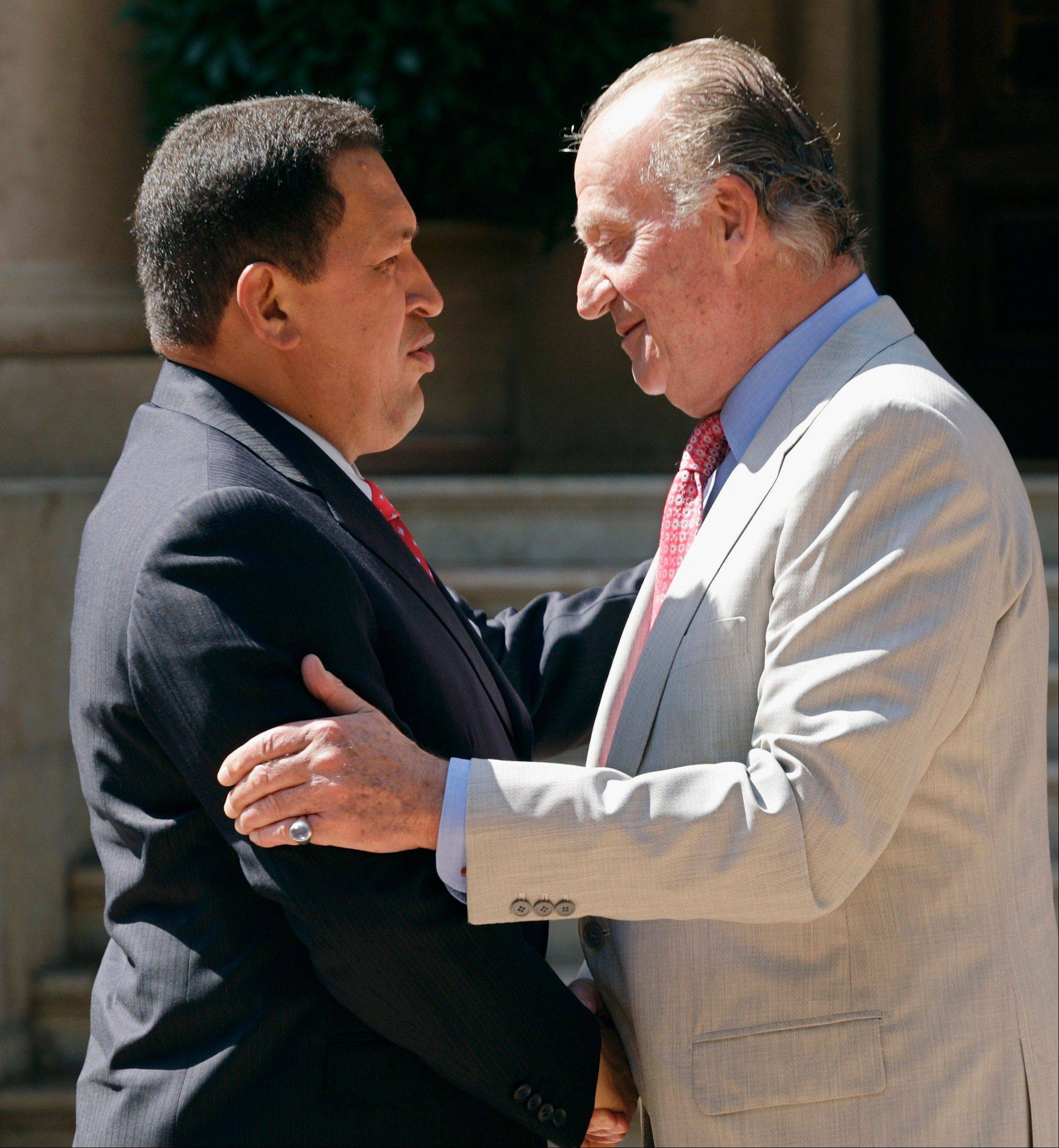 In this July 25, 2008 file photo, Spain's King Juan Carlos, right, shakes hands with Venezuela's President Hugo Chavez at the Marivent Palace in Palma de Mallorca, Spain.