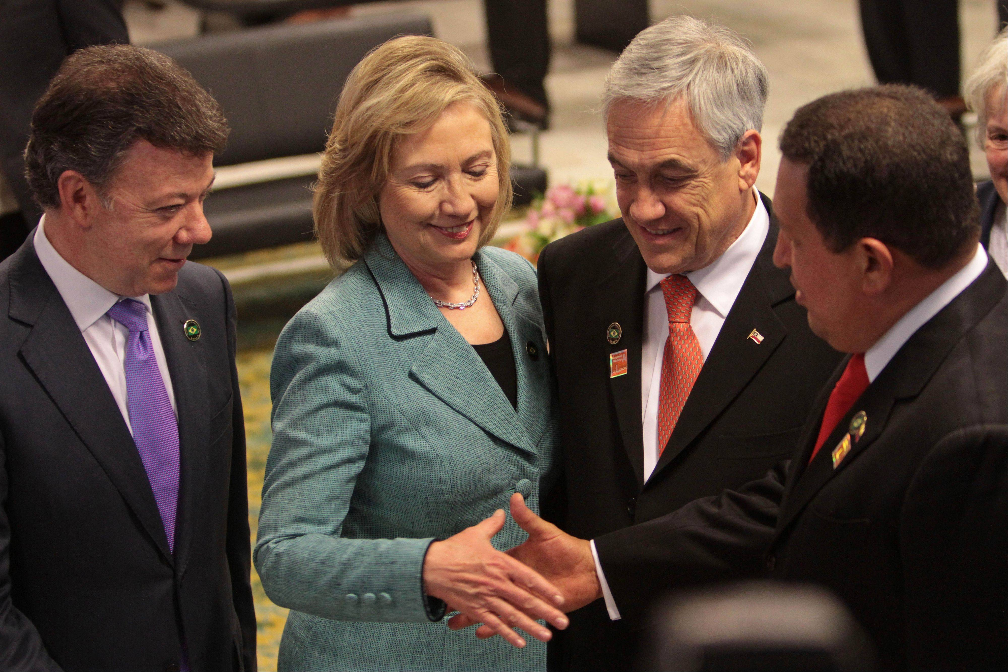 In this Jan. 1, 2011 file photo, U.S. Secretary of State Hillary Clinton, second from left, shakes hands with Venezuela's President Hugo Chavez next to Colombia's President Juan Manuel Santos, left, and Chile's President Sebastian Pinera at the inauguration ceremony of Brazil's President Dilma Rousseff in Brasilia, Brazil.