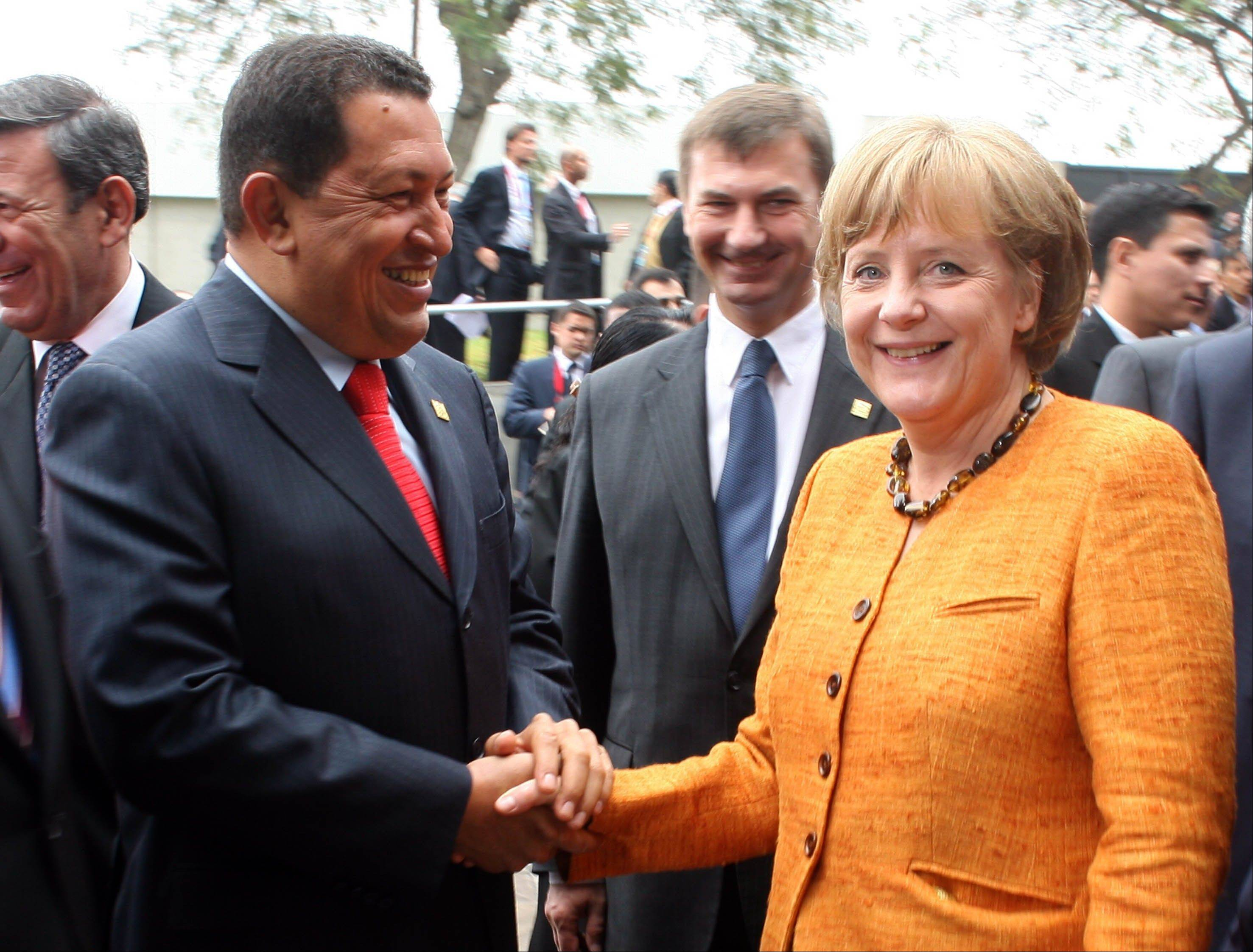 In this May 16, 2008 file photo released by Miraflores Press Office, Venezuela's President Hugo Chavez shakes hands with Germany's Chancellor Angela Merkel before the opening session of the Fifth Latin America and European Summit in Lima.