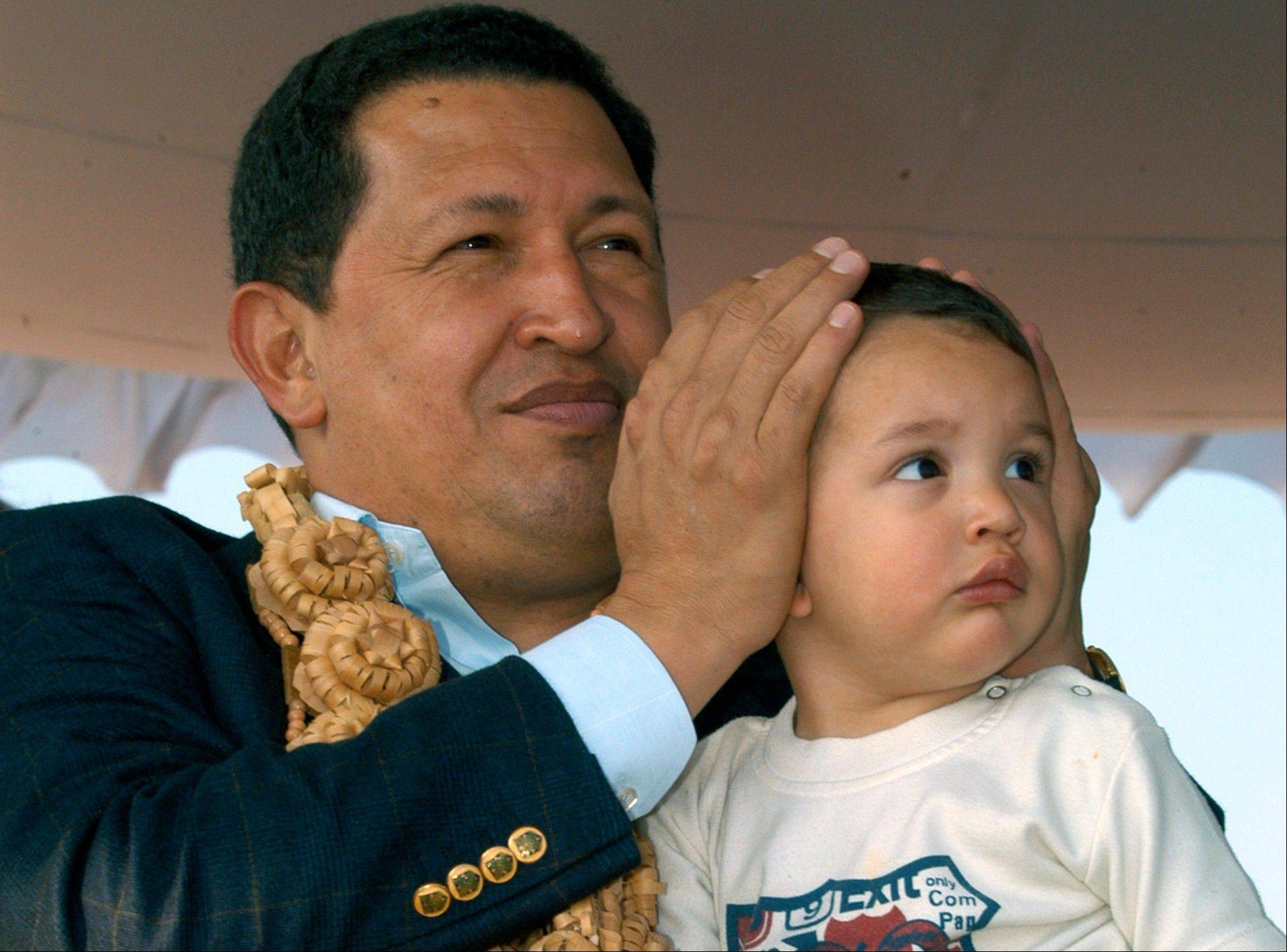 In this March 7, 2005 file photo, Venezuela's President Hugo Chavez covers the ears of his grandson Manolito as they watch a display by Hindustan Aeronautics Limited (HAL) aircrafts at the airport in Bangalore, India.