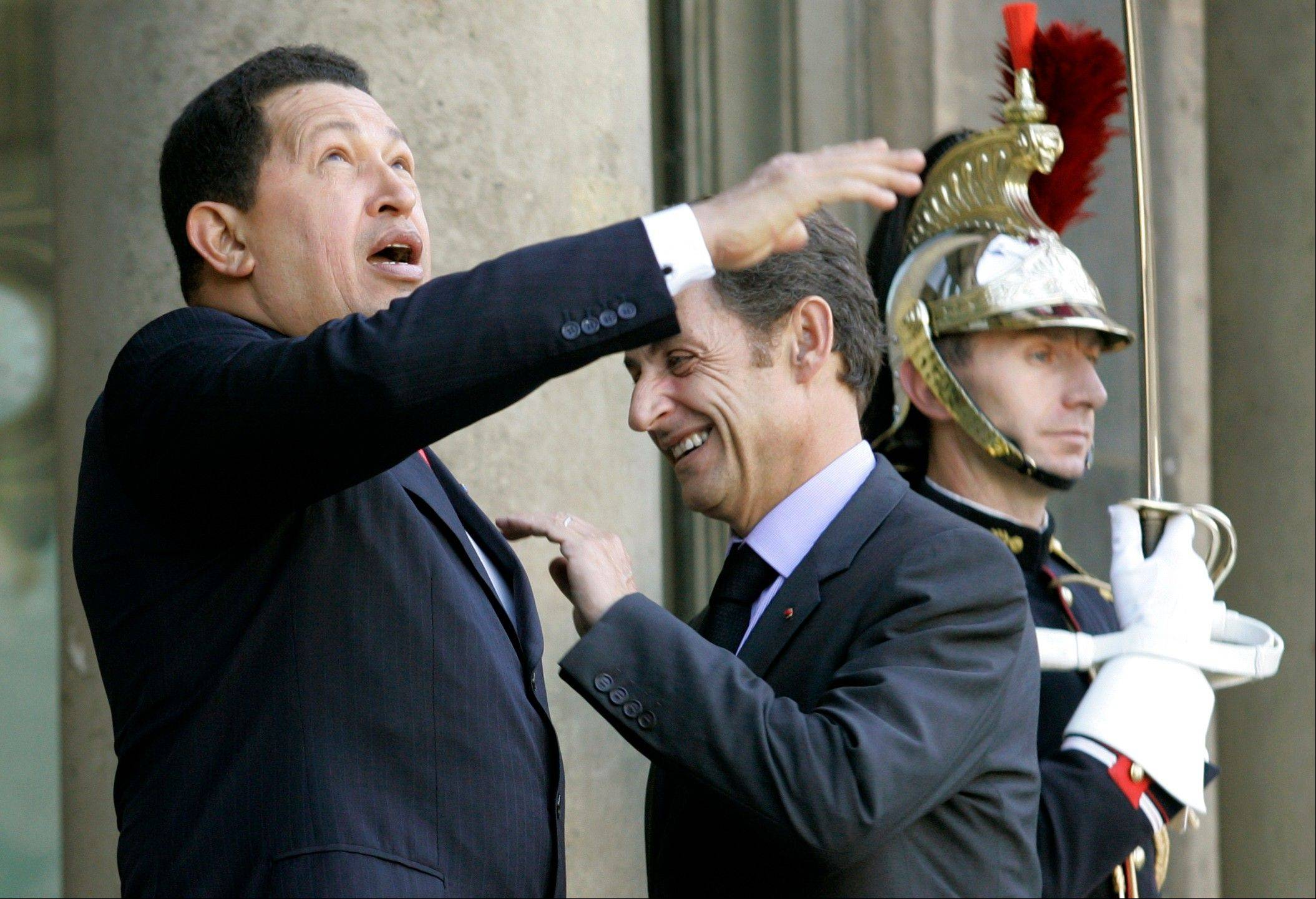 In this Oct. 26, 2008 file photo, France's President Nicolas Sarkozy, center, and Venezuela's President Hugo Chavez have a light moment prior to their meeting at the Elysee palace in Paris, France.
