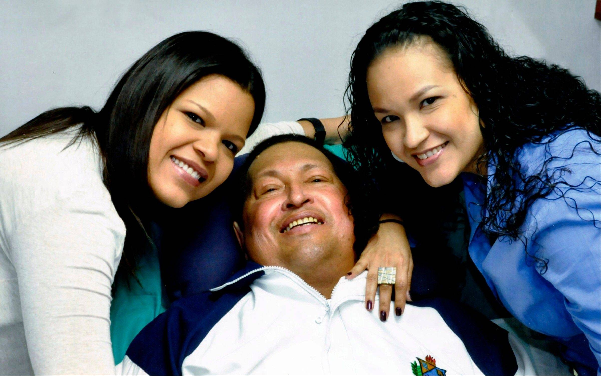 In this file photo released on Feb. 15, 2013 by Miraflores Presidential Press Office, Venezuela's President Hugo Chavez, center, poses for a photo with his daughters, Maria Gabriela, left, and Rosa Virginia in Havana, Cuba,