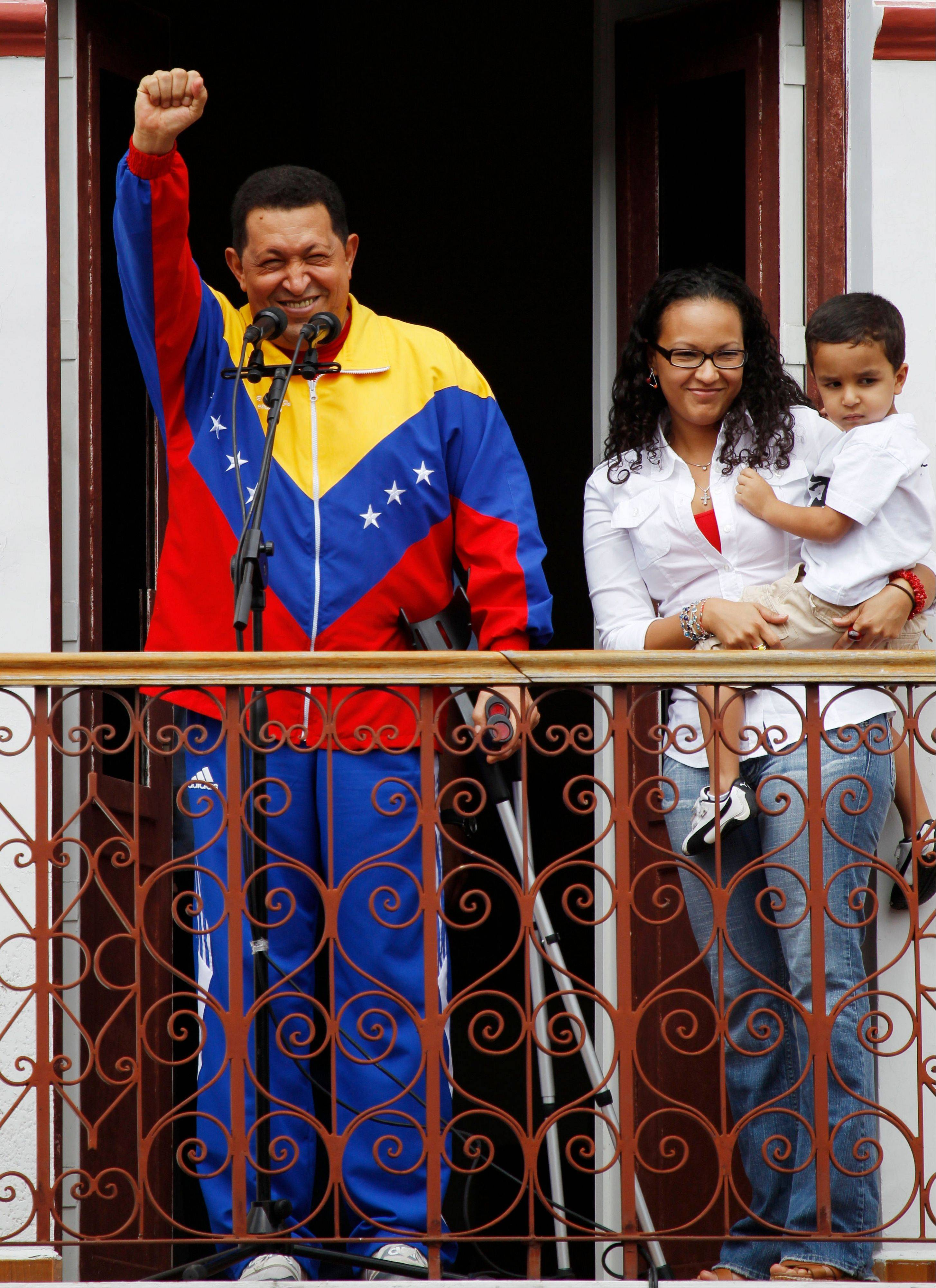 "In this May 22, 2011 file photo, Venezuela's President Hugo Chavez greets supporters next to his daughter Maria and grandson Jorge after his radio and television program ""Hello President!,"" his first public appearance after injuring himself while jogging two weeks earlier."