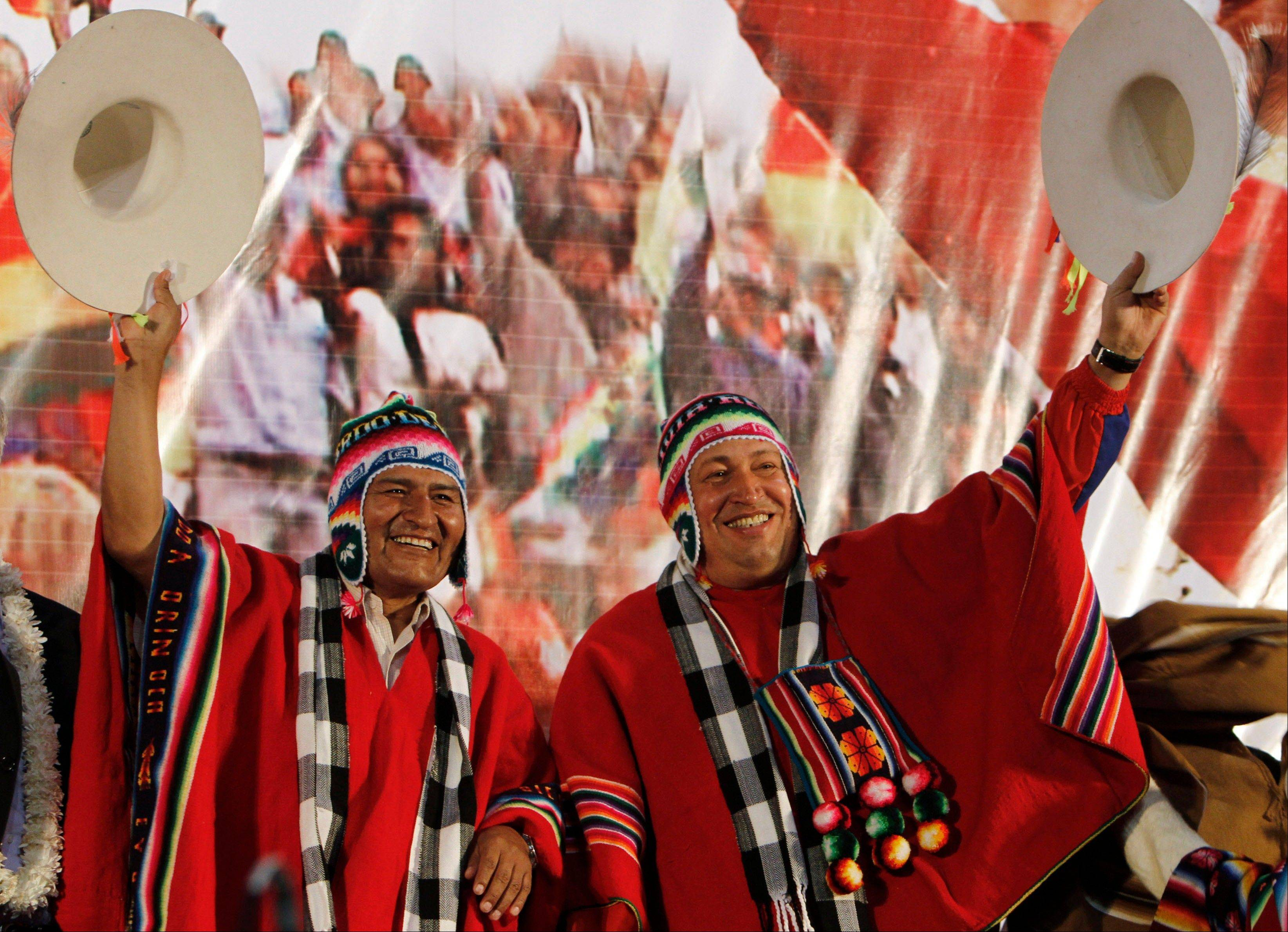 In this March 31, 2011 file photo, Venezuela's President Hugo Chavez, right, and Bolivia's President Evo Morales, dressed in traditional Quechua indigenous clothing, wave to supporters at a welcoming ceremony for Chavez in Cochabamba, Bolivia.