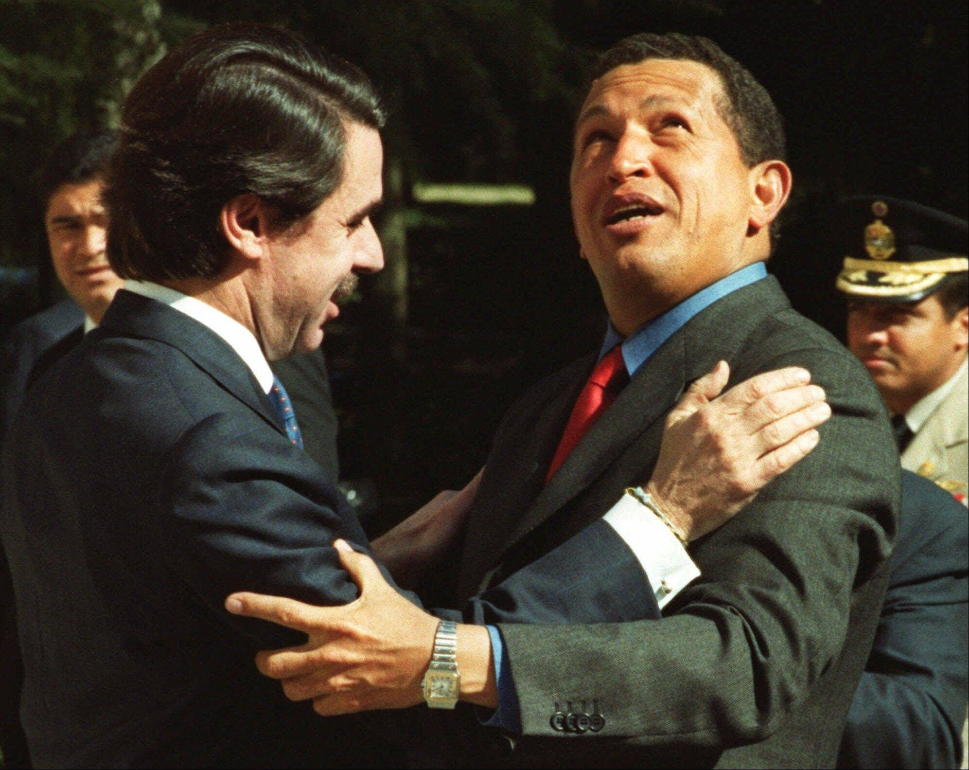 In this Feb. 21, 2000 file photo, Venezuela's President Hugo Chavez, right, looks up while being embraced by Spain's Prime Minister Jose Maria Aznar during Chavez's visit to the Moncloa palace in Madrid, Spain.