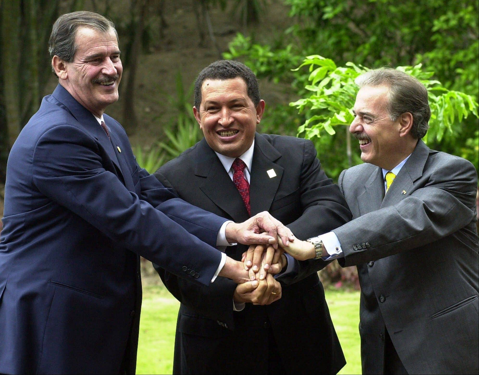 In this April 8, 2001 file photo, Mexico's President Vicente Fox, left, Venezuela's President Hugo Chavez, center, and Colombia's President Andres Pastrana shake hands as they pose for a photo in Caracas, Venezuela.