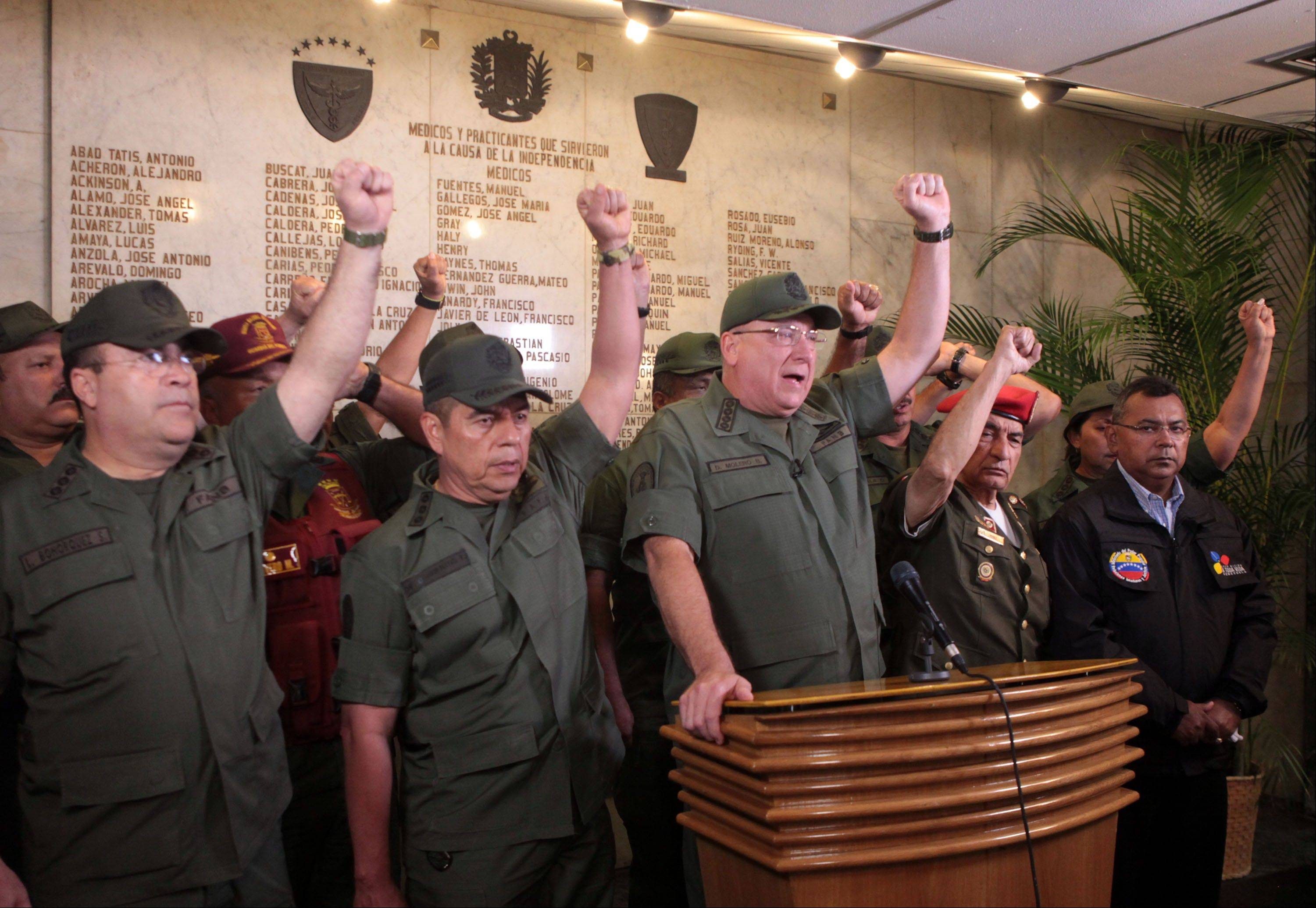 In this photo released by Miraflores Presidential Press Office, Venezuela's Defense Minister Admiral Diego Molero, at the podium, gestures alongside other military leaders during a live televised message to the nation after the vice president announced the death of President Hugo Chavez in Caracas, Venezuela.