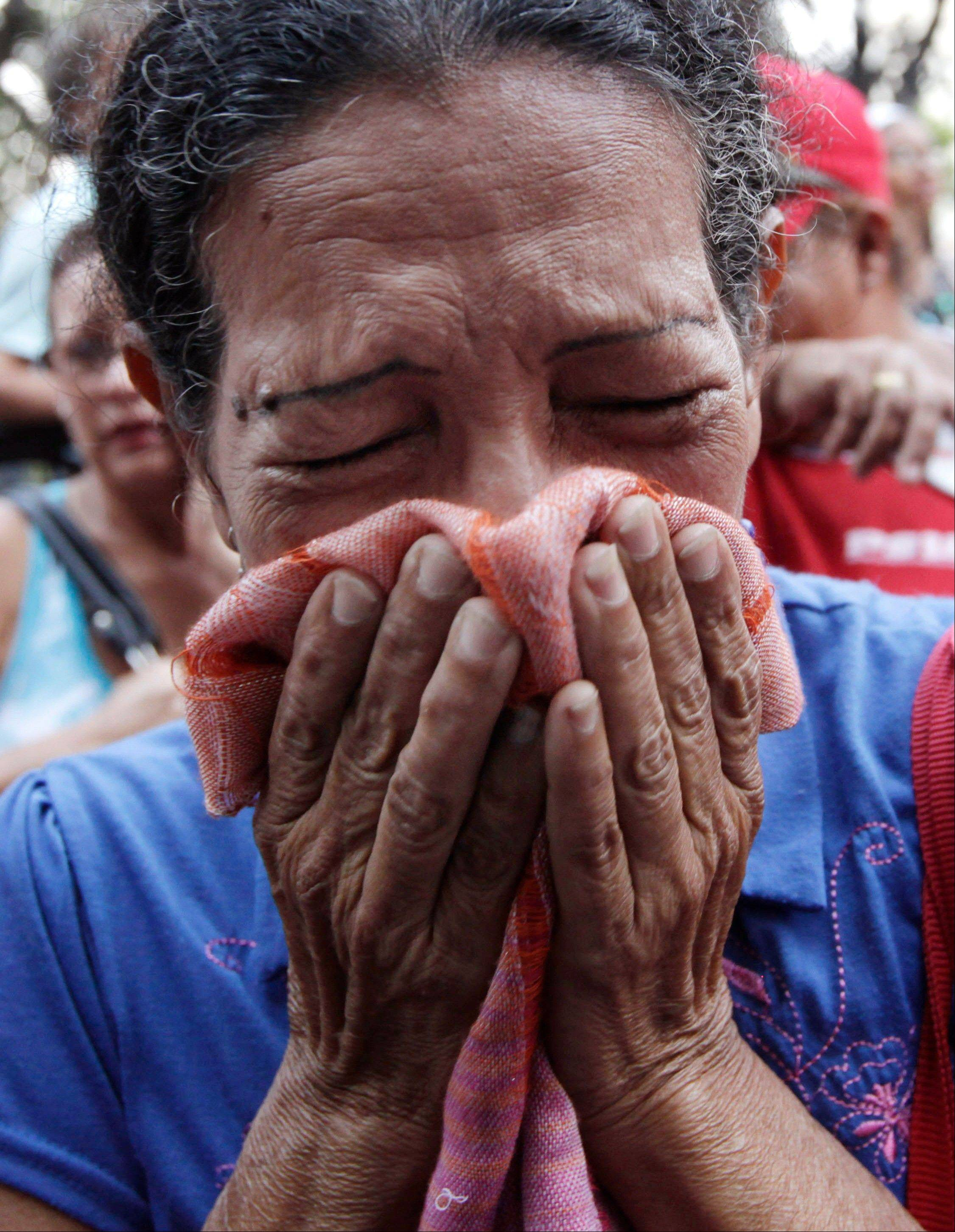 A supporter of Venezuela's President Hugo Chavez cries as she learns that Chavez has died through an announcement by the vice president in Caracas, Venezuela.