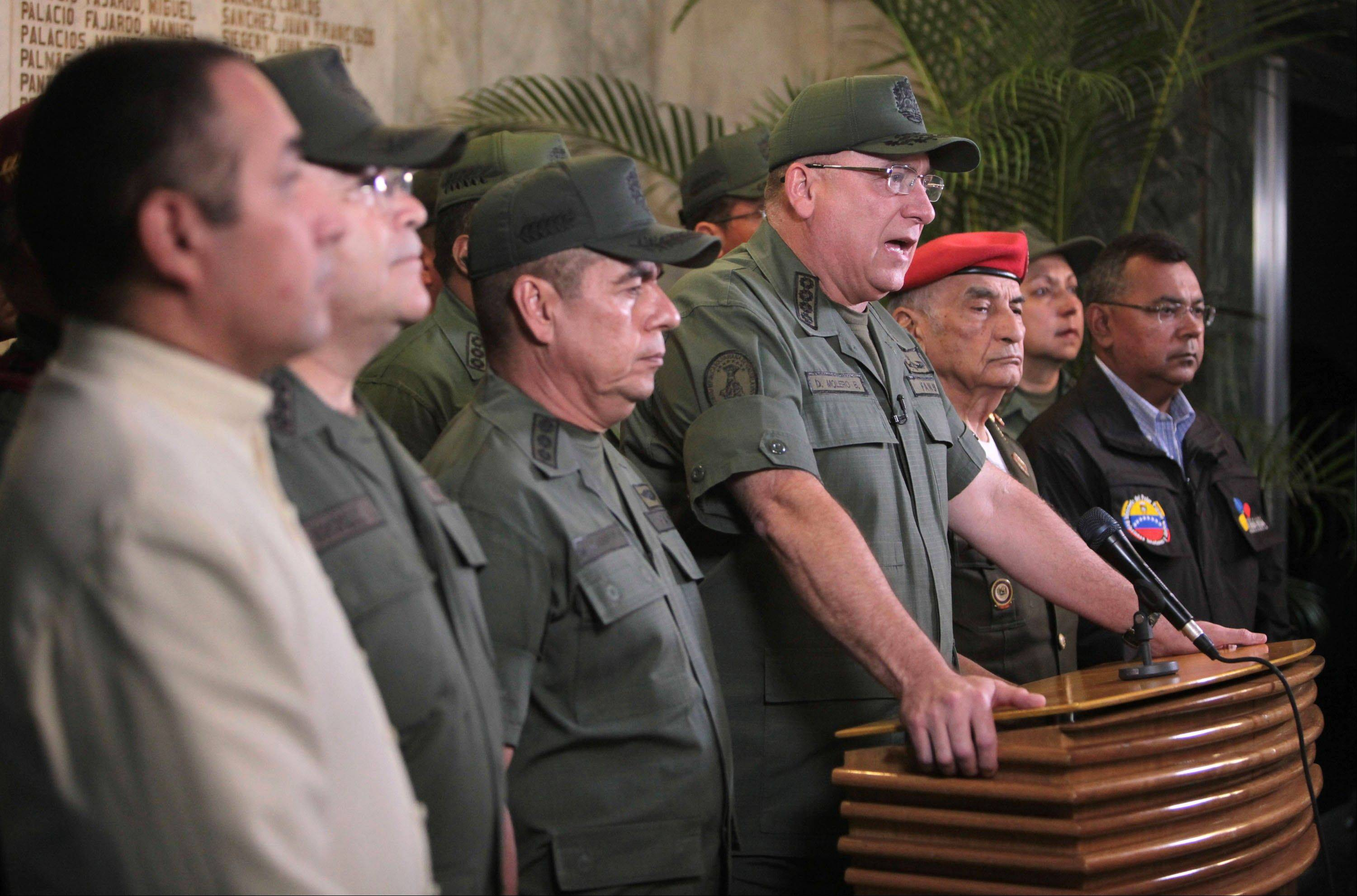 In this photo released by Miraflores Presidential Press Office, Venezuela's Defense Minister Admiral Diego Molero, at the podium, speaks as he is flanked by other military leaders during a live televised message to the nation after the vice president announced the death of President Hugo Chavez in Caracas, Venezuela.