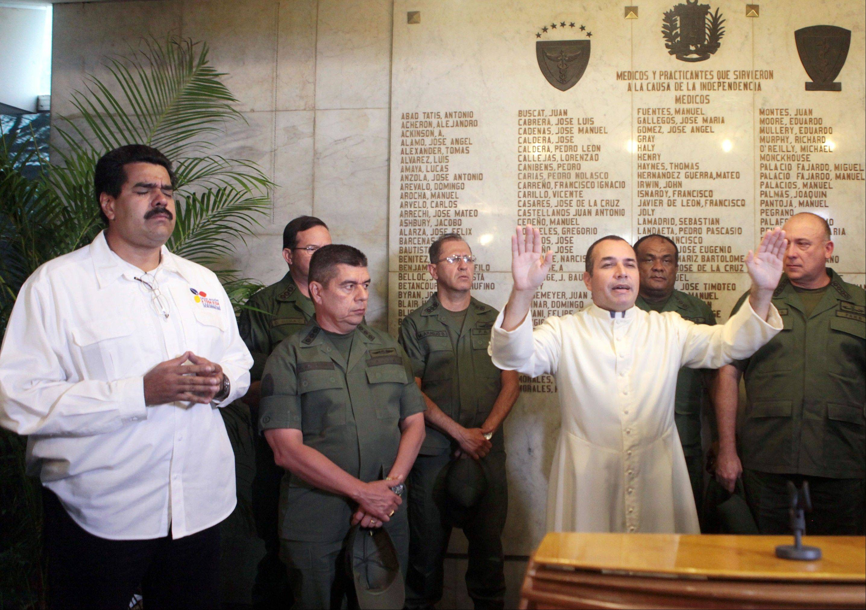In this photo released by Miraflores Presidential Press Office, a priest prays next to Venezuela's Vice President Nicolas Maduro, left, and military officers after Maduro addressed the nation to announce the death of President Hugo Chavez in Caracas, Venezuela.