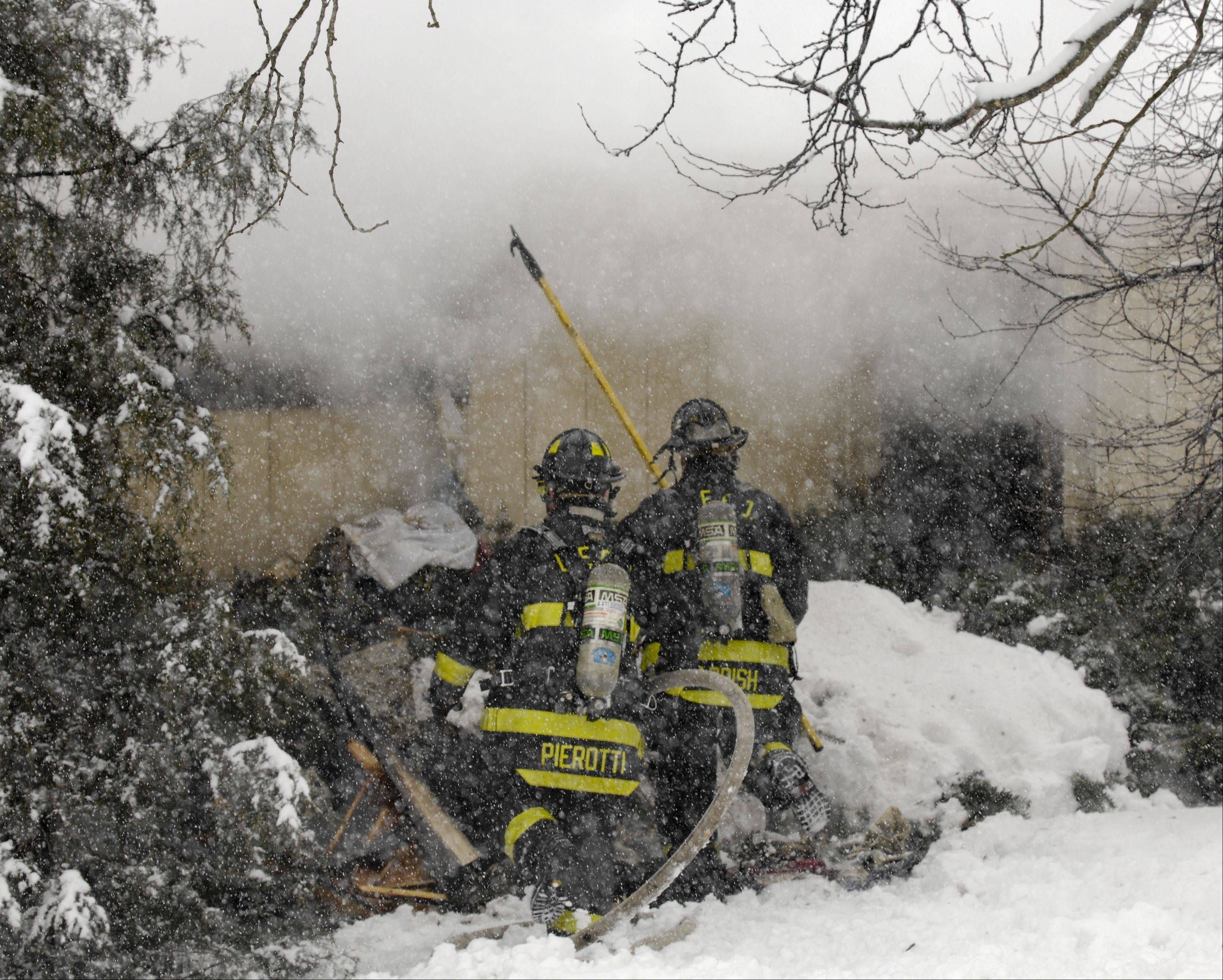 Firefighters battle a house fire Tuesday in an unincorporated area near Glen Ellyn. The fire caused extensive damage to a one-story home, but no injuries were reported.
