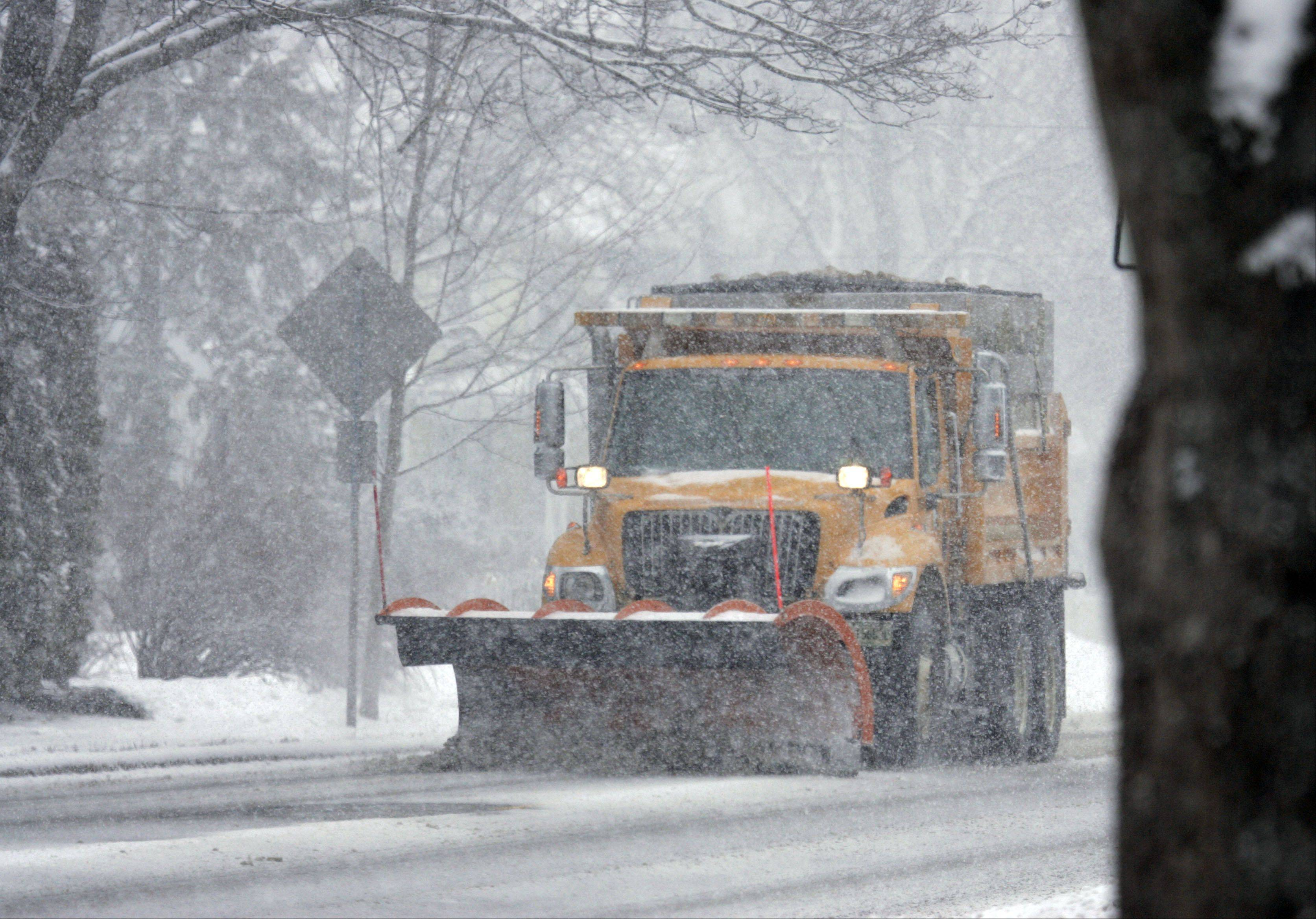 A plow clears Prairie Street in St. Charles as the area prepares for the big storm Tuesday.