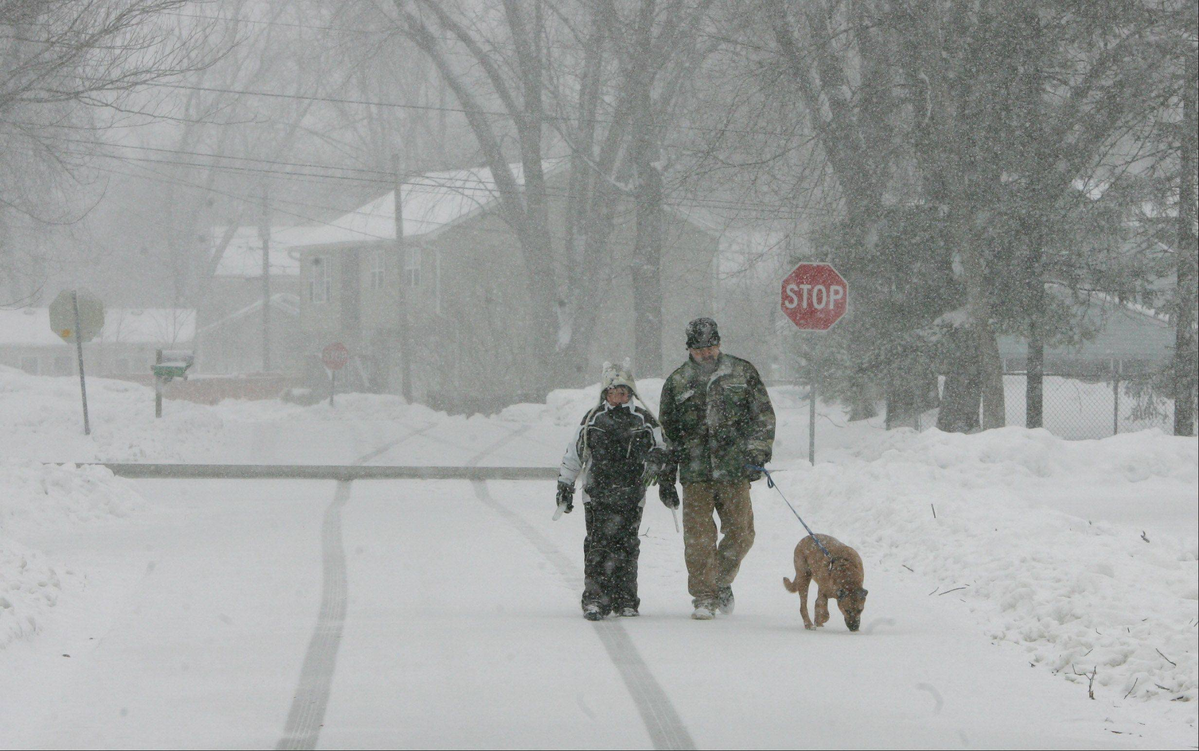 Henry Arimas, of Lake Villa, and his son, Henry Jr., walk with their dog, Amarillo, as snow falls Tuesday in Lake County. The winter storm caused schools and some businesses to close for the day.