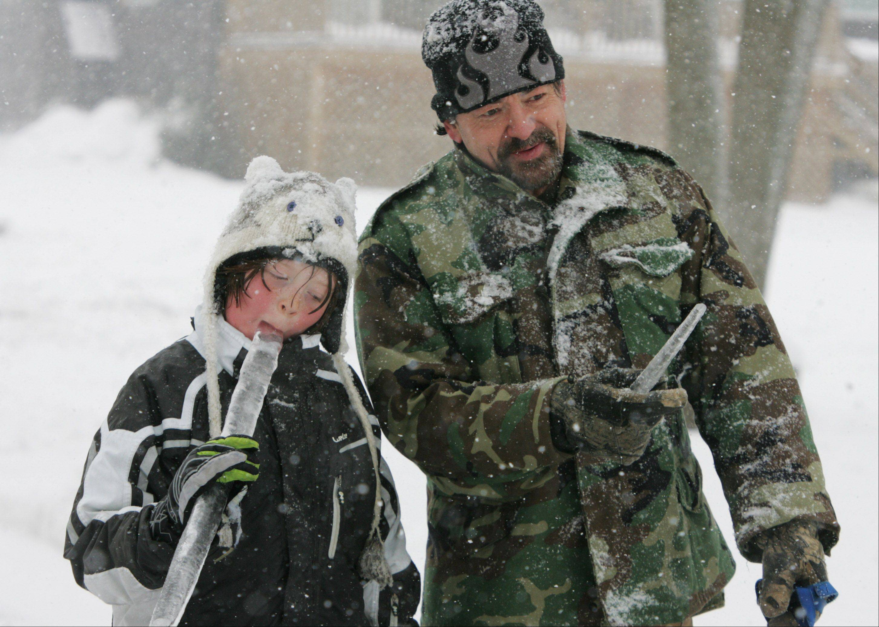 Henry Arimas, of Lake Villa, and his son, Henry Jr., eat icicles while they walk their dog, Amarillo, as snow falls Tuesday in Lake County. The winter storm caused schools and some businesses to close for the day.