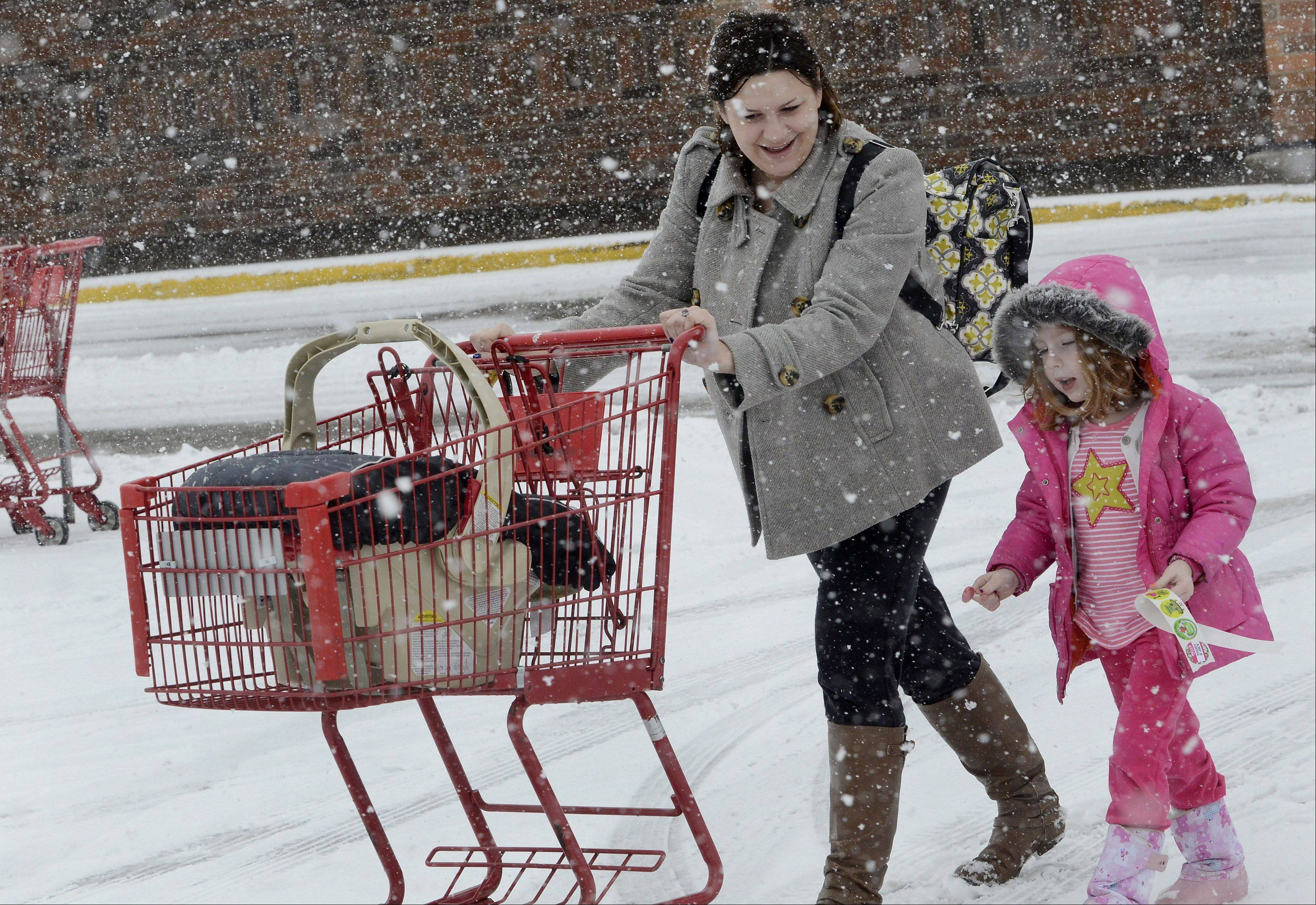 Jessica Thrush of Island Lake and her daughter Sophia brave the snow Tuesday to go shopping in Lake Zurich.