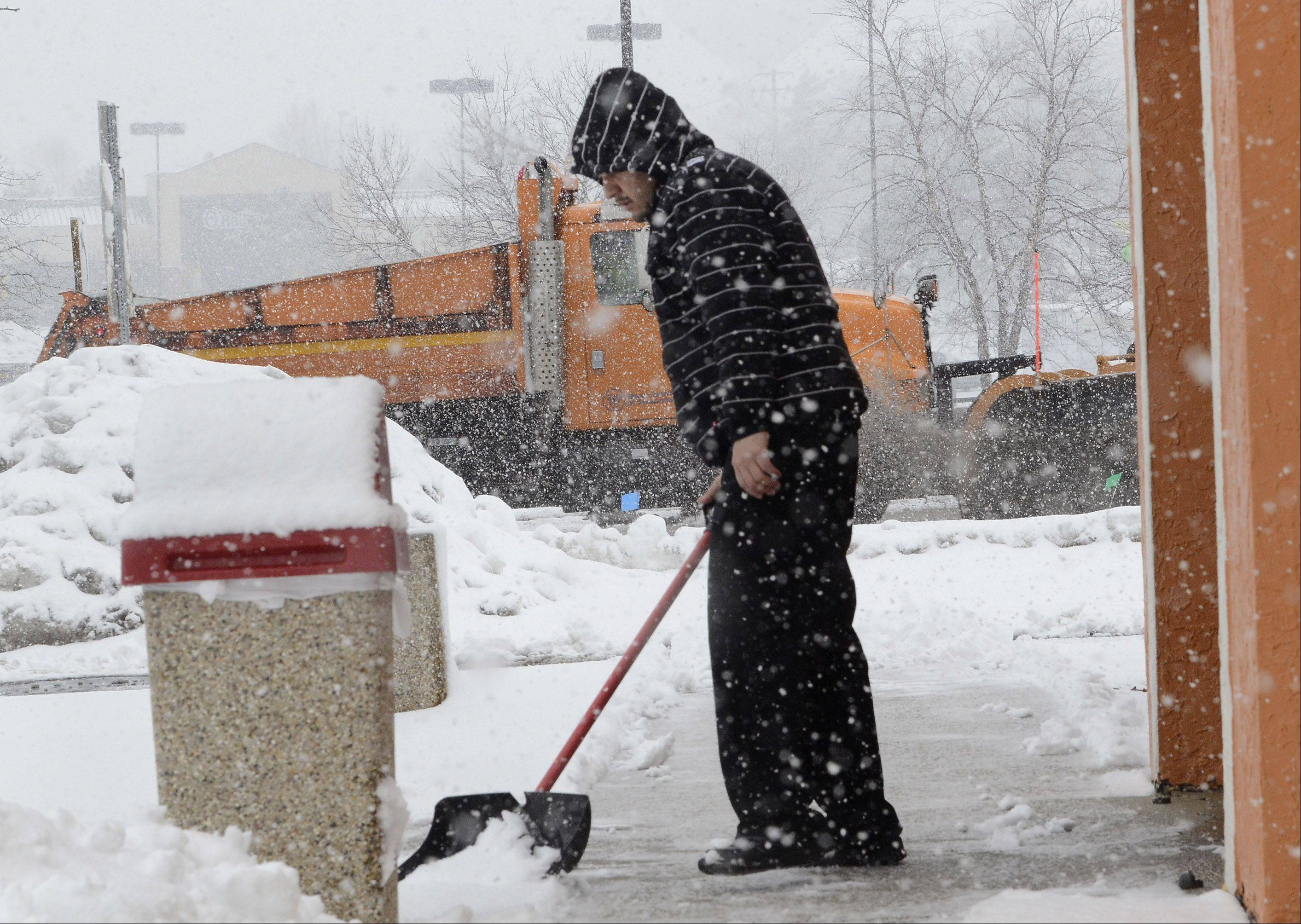 Armando Lopez shovels the walk in front of the Taco Bell in Lake Zurich, as a snowplow drives by on Rt. 22.
