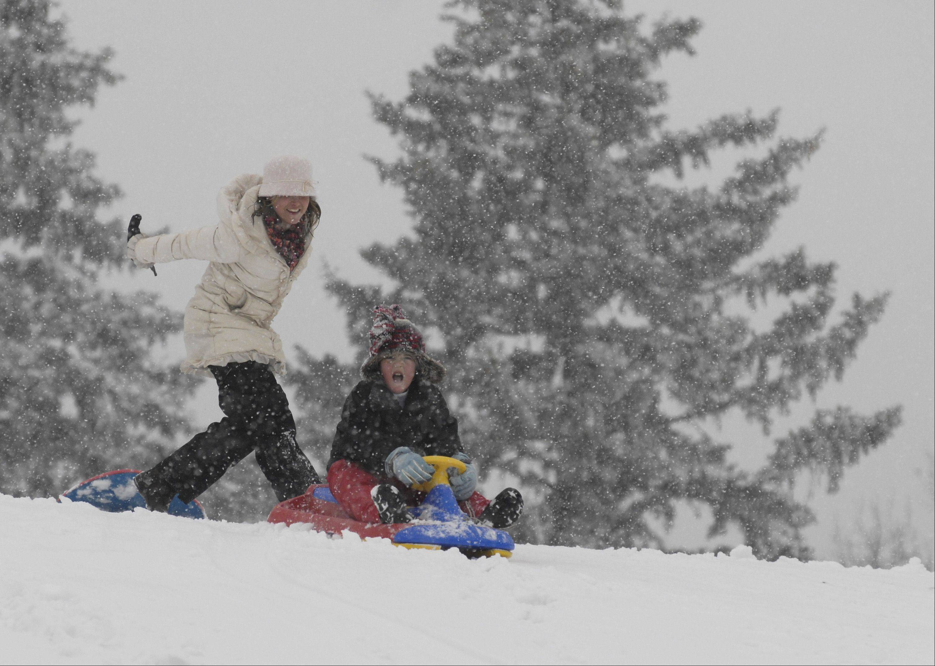 Lynell Iannicelli gives Logan Lawrence, 5, a push as he heads down the sledding hill at Newton Park in Glen Ellyn on Tuesday.